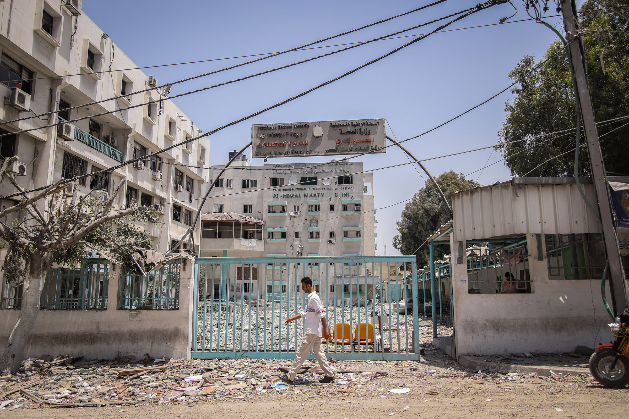 A pedestrian passes in front of the Al-Remal Clinic, Gaza's sole Covid-19 testing laboratory, damaged following Israeli airstrikes, in Gaza City, Gaza, on May 21, 2021.