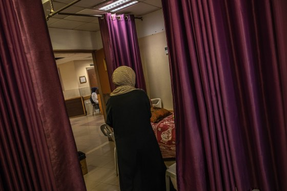 Drapes hang as Palestinians, who were wounded in overnight Israeli air strikes on the Gaza Strip, receives treatment at Al-Shifa Hospital on May 18, 2021.
