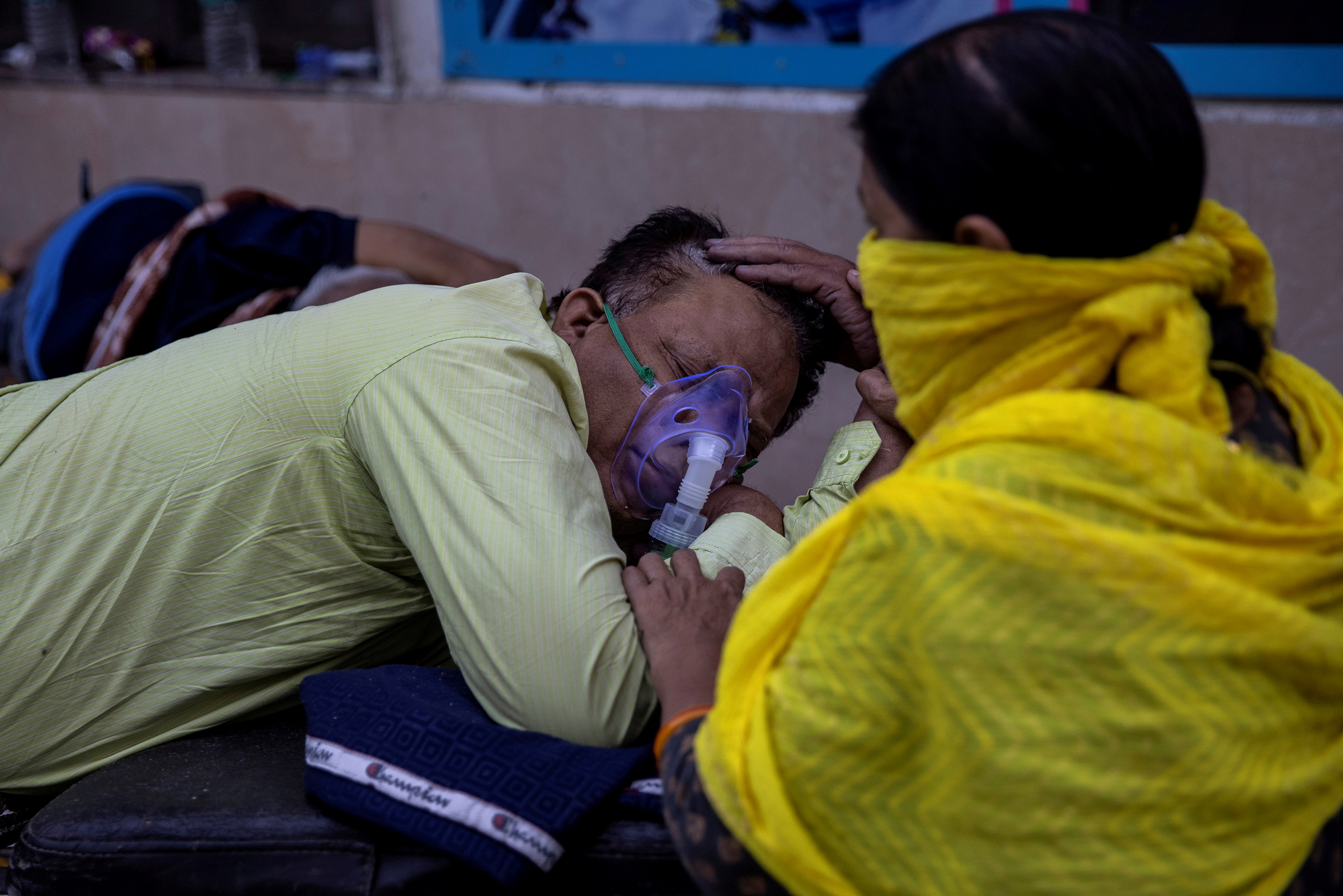 A woman takes care of her husband, who is suffering from COVID-19, as he waits to be admitted outside the casualty ward at Guru Teg Bahadur hospital in New Delhi on April 23, 2021.