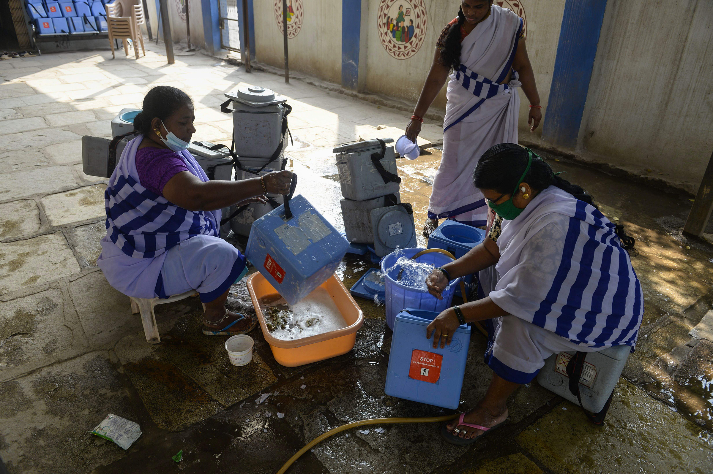 ASHA workers clean carriers for the COVID-19 vaccine at a health center in Hyderabad on Jan. 29, 2021.