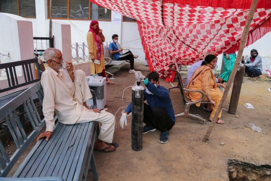 COVID-19 patients receive oxygen outside a government run hospital in Jammu, India, on May 12, 2021.