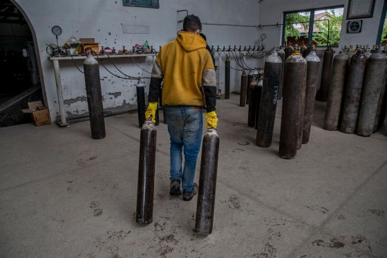 A worker moves empty oxygen cylinders for refilling at a gas supplier facility in Srinagar on May 11, 2021.