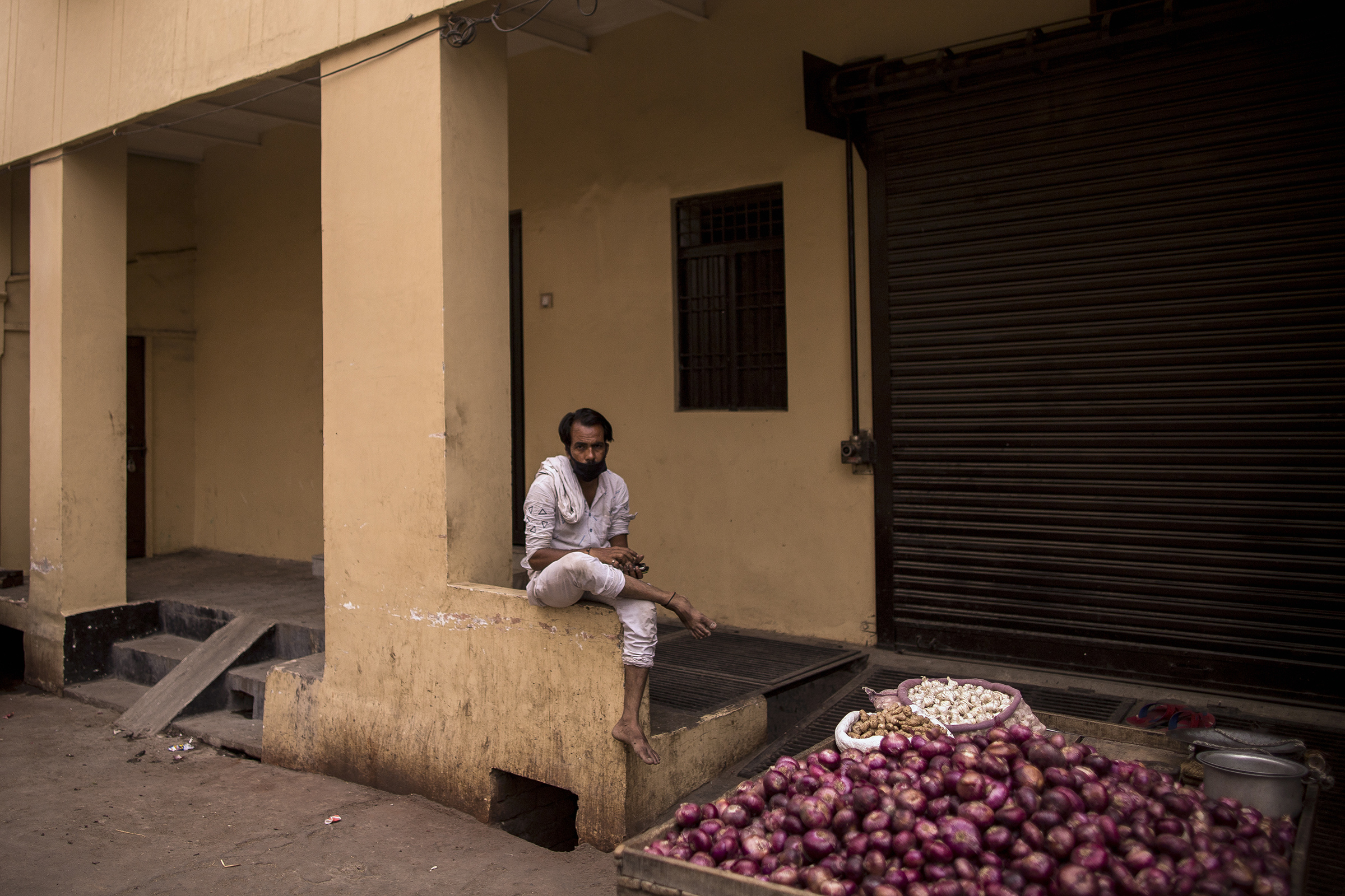 An onion vendor waits for customers on a deserted street during a lockdown in Agra, Uttar Pradesh, on May 3, 2021.