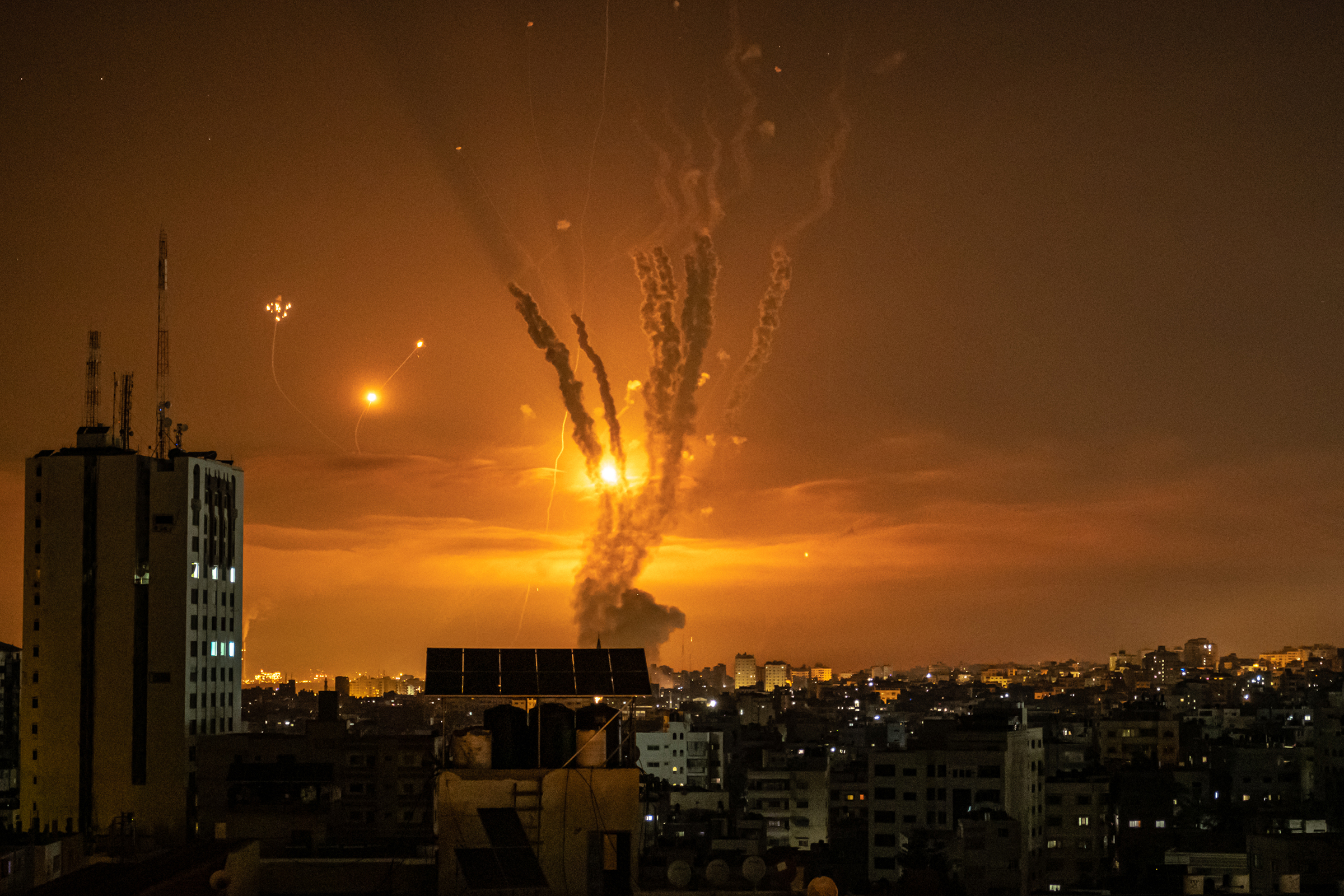 Rockets launched toward Israel from the northern Gaza Strip, and the response from the Israeli missile-defense system known as the Iron Dome, leave streaks through the sky in Gaza City on May 14.