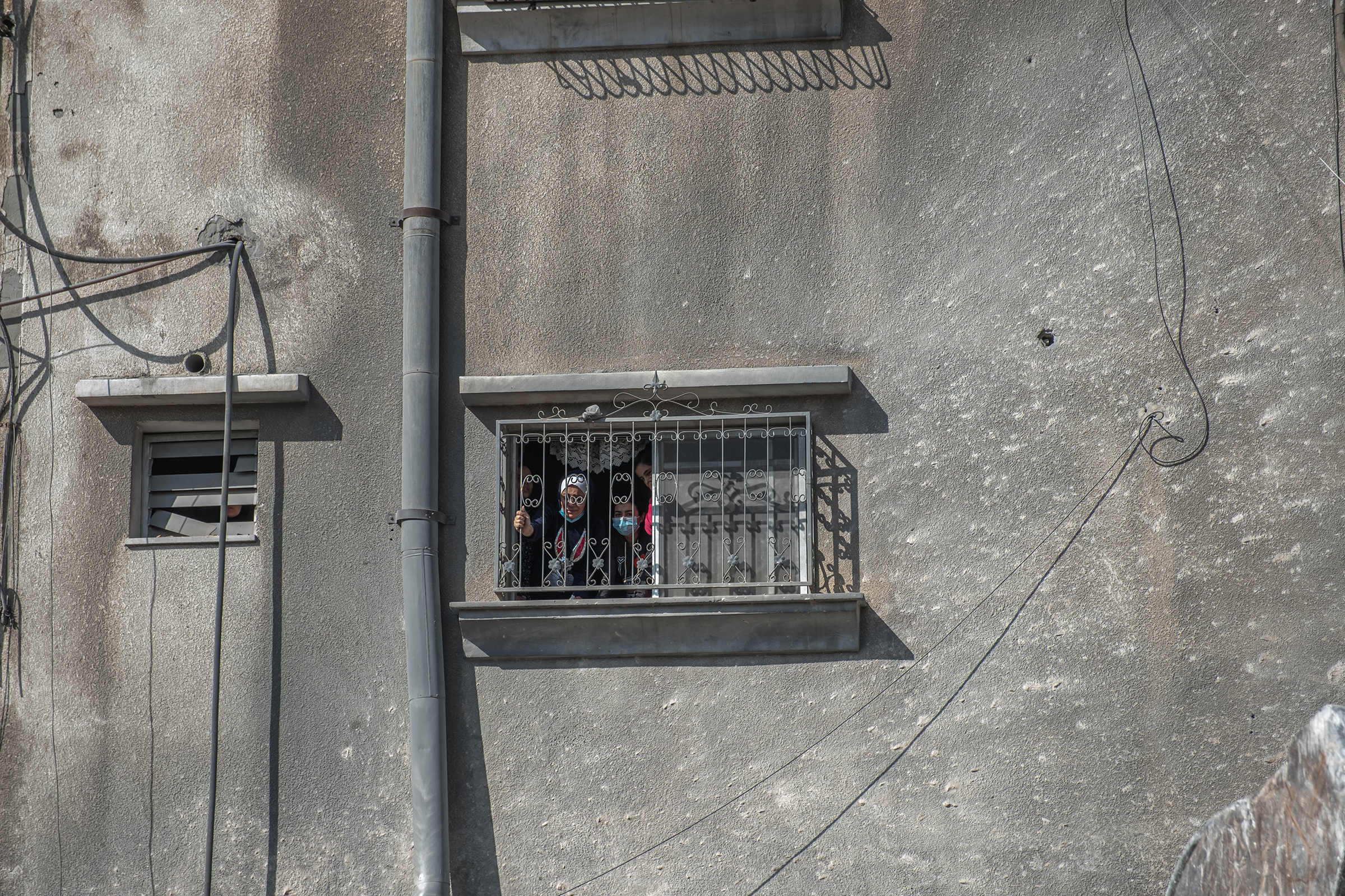 Palestinian women look out from a window at the rubble of a destroyed house in Gaza City on May 16.
