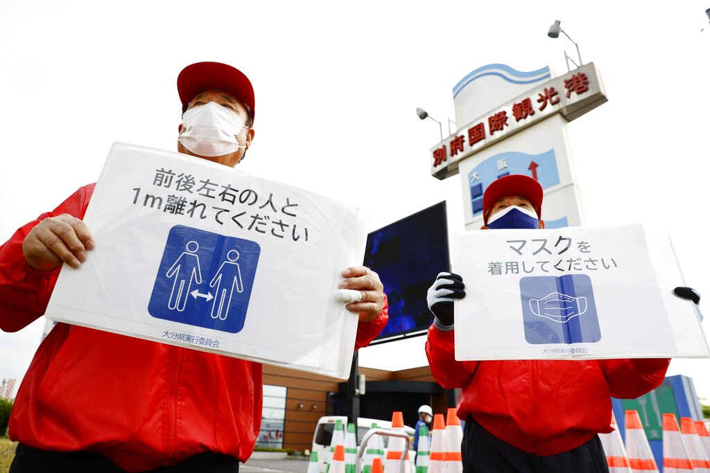 Organizing staff members of the Tokyo Olympic torch relay hold signs urging spectators to wear masks and maintain social distancing in the Oita Prefecture city of Beppu, southwestern Japan, on April 23, 2021, amid the coronavirus pandemic.