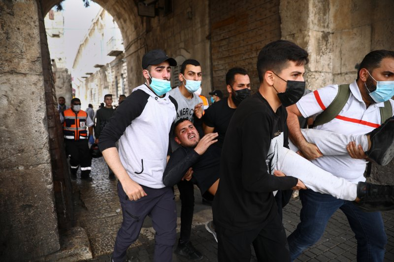 Palestinians evacuate a wounded protester during clashes with Israeli security forces at the Lions Gate in Jerusalem's Old City, Monday, May 10, 2021. Israeli police clashed with Palestinian protesters at a flashpoint Jerusalem holy site on Monday, the latest in a series of confrontations that is pushing the contested city to the brink of eruption. The latest violence at the Al-Aqsa Mosque compound came after days of mounting tensions between Palestinians and Israeli authorities in the Old City of Jerusalem.