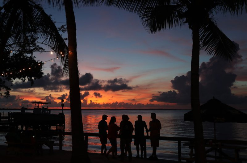 People enjoy the sunset over the water in the Gulf of Mexico during the seasonal king tides on October 27, 2019 in Key Largo, Florida.