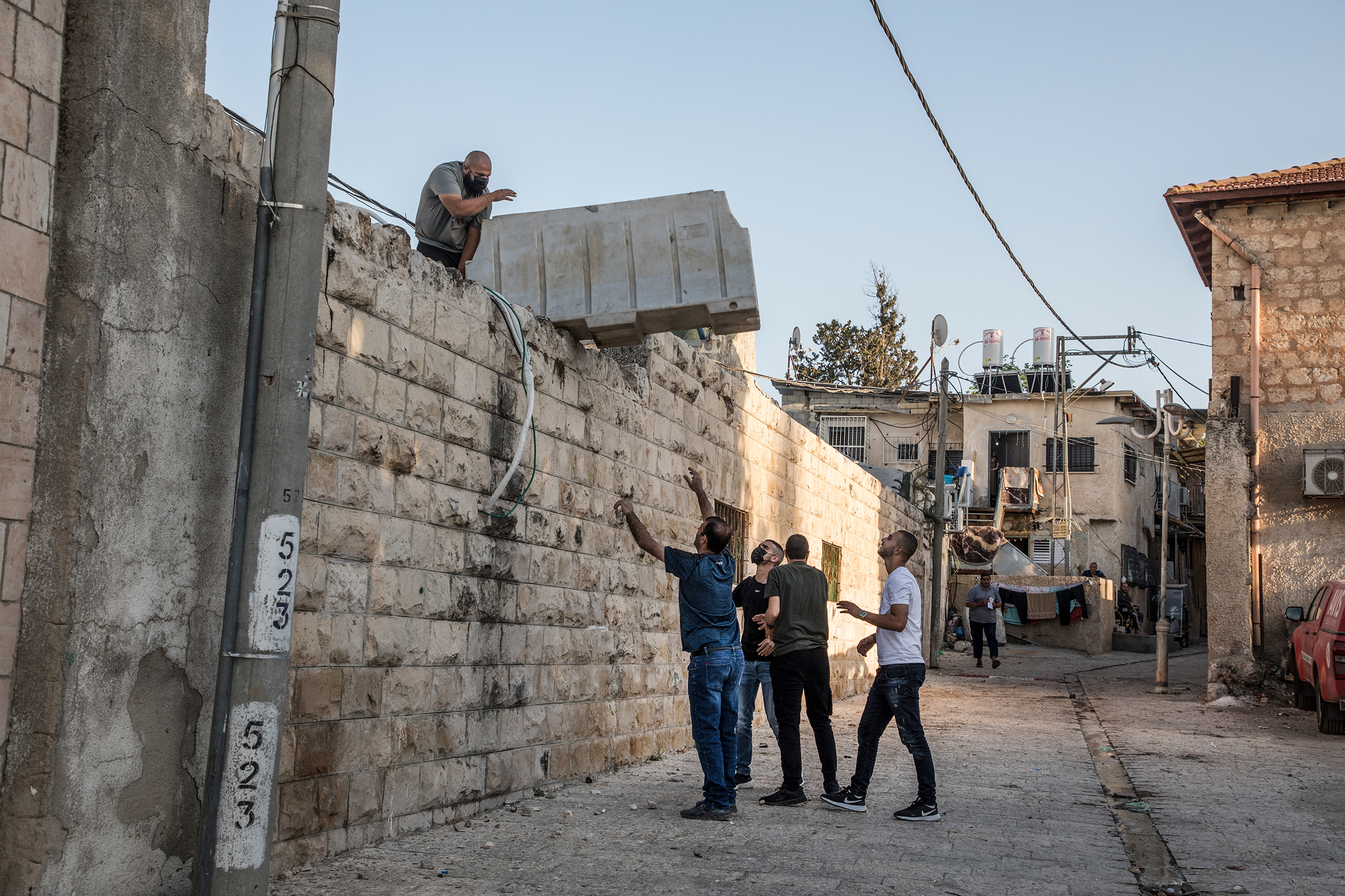 At the mosque in the old city center of Lod, young Palestinians gather on the roof to prepare their defense before expected clashes on May 12, 2021.