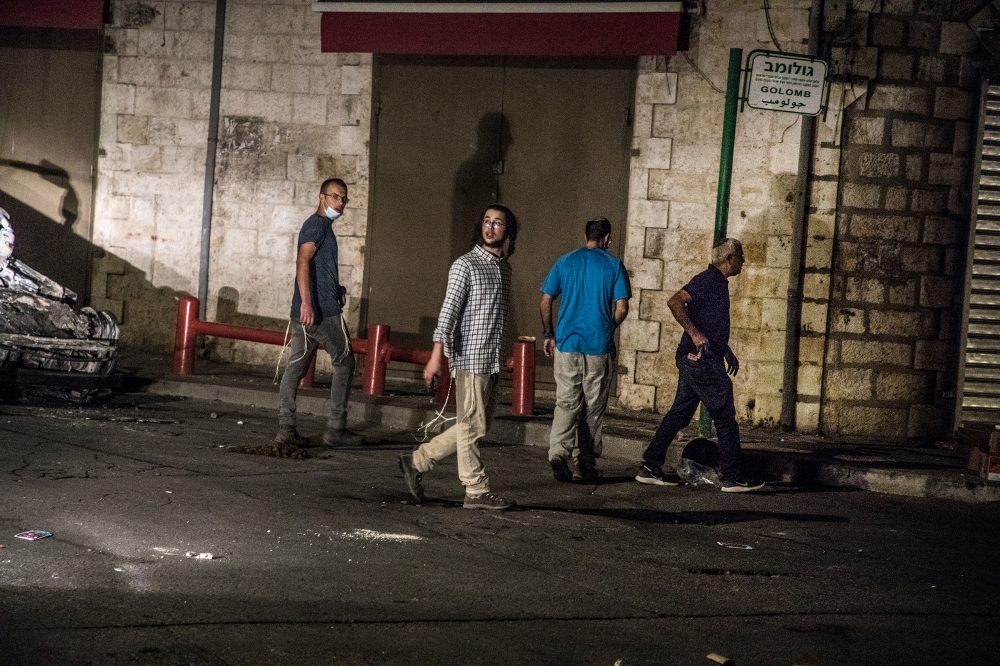 Young Jewish men from a group comprising settlers and extreme right-wing activists, mostly armed, try to approach the downtown mosque in the mixed city of Lod, Israel, on May 12, 2021.