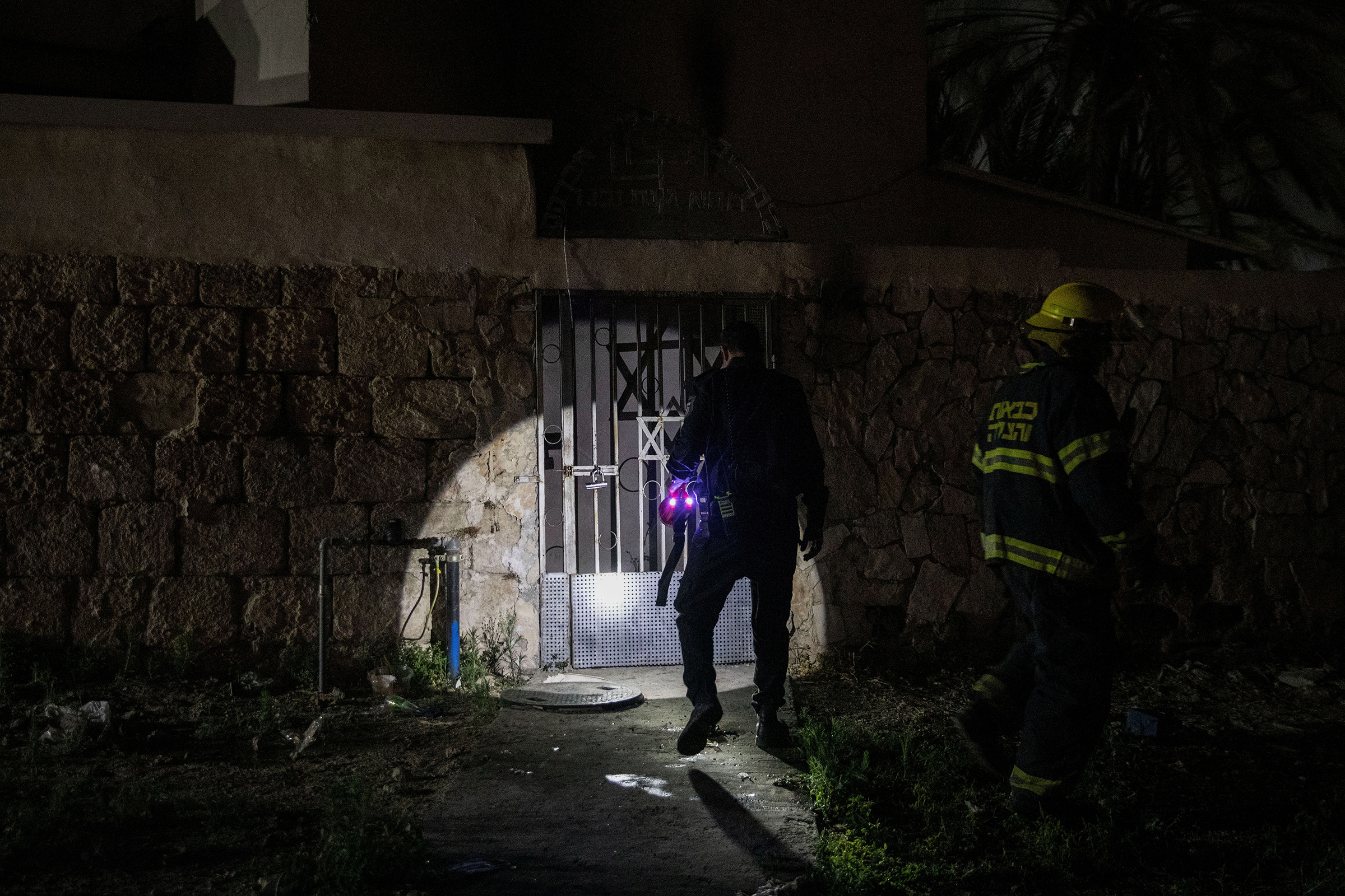 Firefighters inspect a synagogue after it was set on fire in Lod on May 14, 2021.