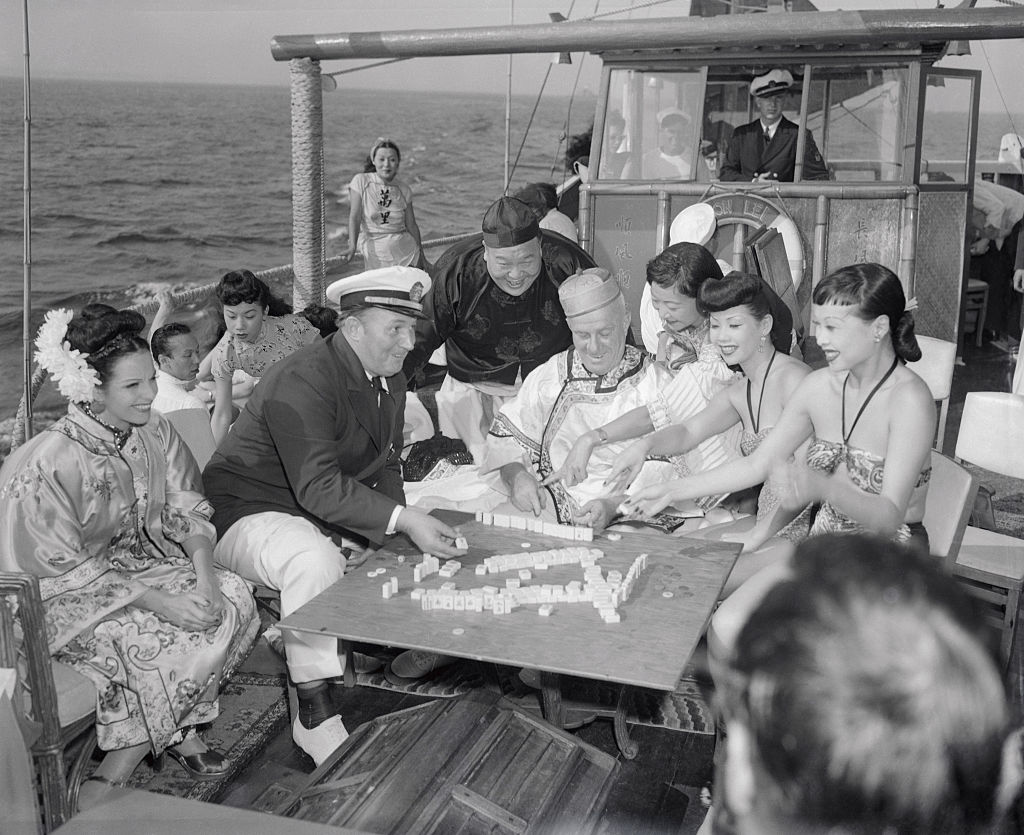 Robert L. Ripley (seated, in captain's hat) and various guests enjoy a game of mah-jongg aboard the Mon Lei, a junk (type of Chinese sailing ship) he brought across the Pacific from Kowloon, on a cruise on the Long Island Sound in Aug. 1946. Ripley was known for his eponymous show  Believe it or Not!  which featured  unusual  facts from around the world.