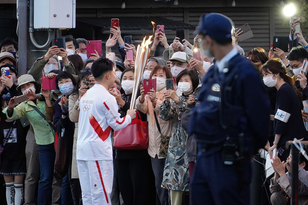 Tokyo Olympics Games Torch Relay audience seen wearing facemasks as a precaution against the spread of covid-19 take photos with their smartphones as a torch bearer shows the torch before the run on April 7, 2021.