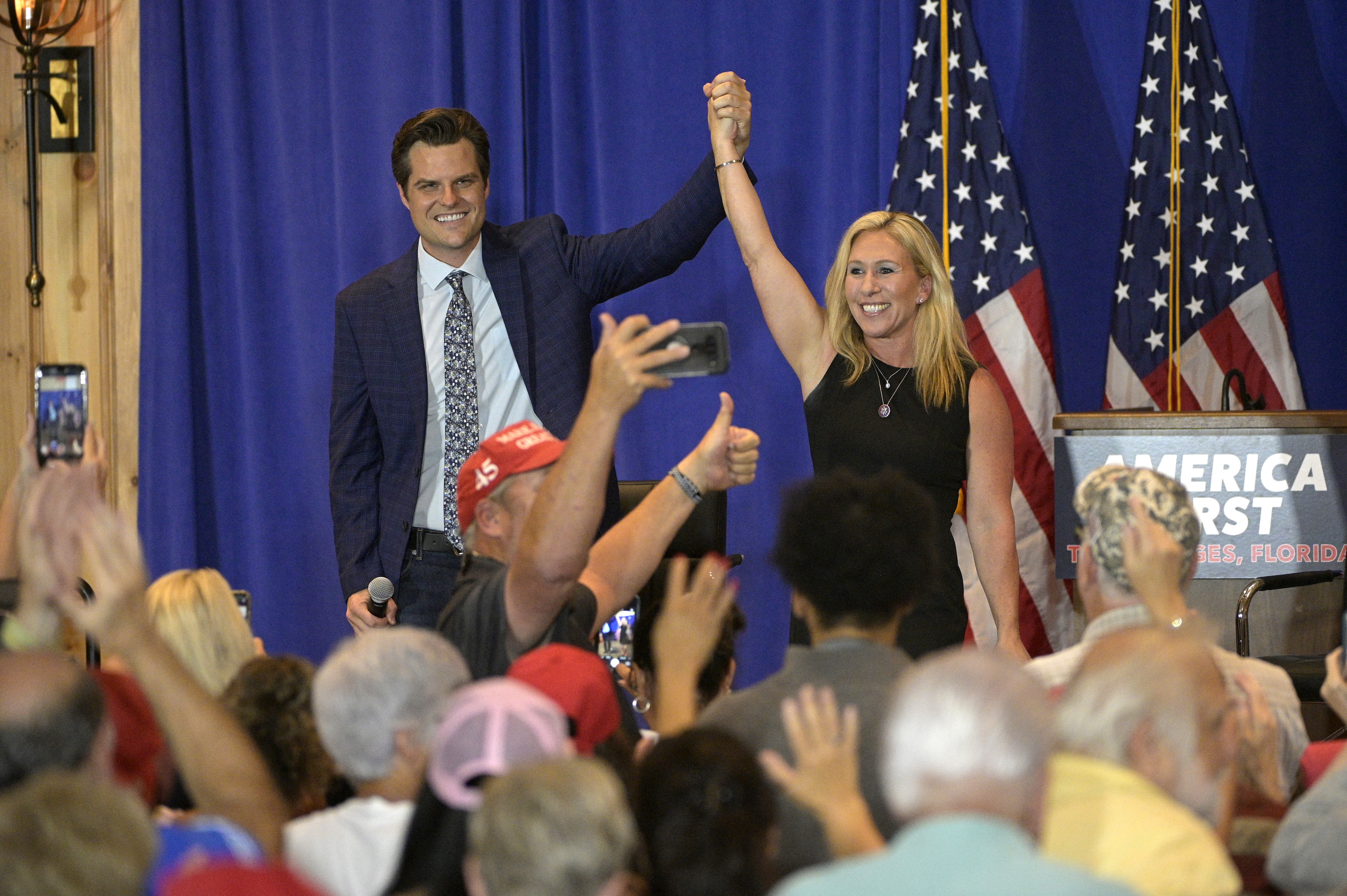 Rep. Matt Gaetz, R-Fla., left, and Rep. Marjorie Taylor Greene, R-Ga., raise their arms after addressing attendees of a rally in The Villages, Fla., on May 7, 2021,