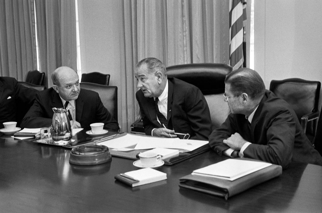 Secretary of Defense Robert McNamara (right), President Lyndon Johnson and Secretary of State Dean Rusk, seated at a table after McNamara's return from South Vietnam, in Washington, on July 21, 1965.