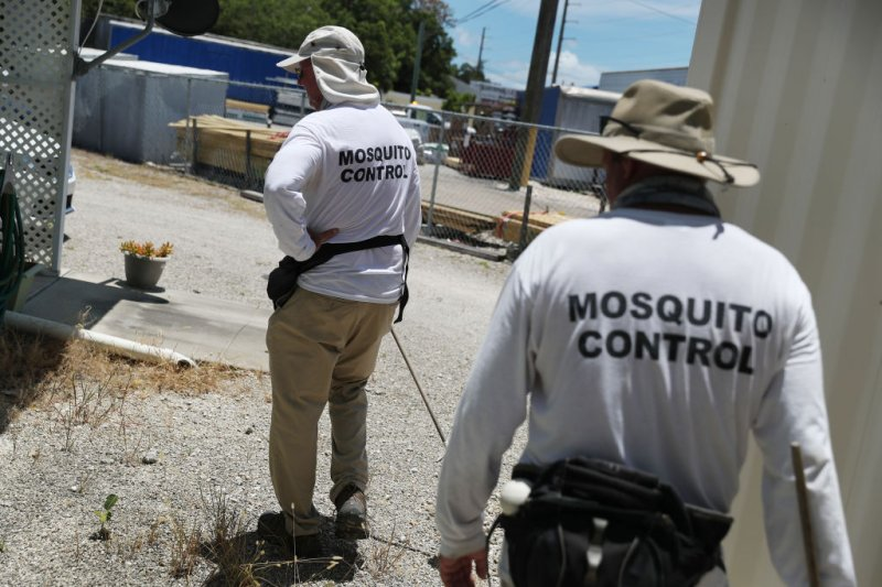 Billy Ryan and Meredith Kruse (L-R) with the Florida Keys mosquito control department inspect a neighborhood for any mosquitos or areas where they can breed as the county works to eradicate mosquitos carrying dengue fever on July 8, 2020 in Key Largo, Florida.