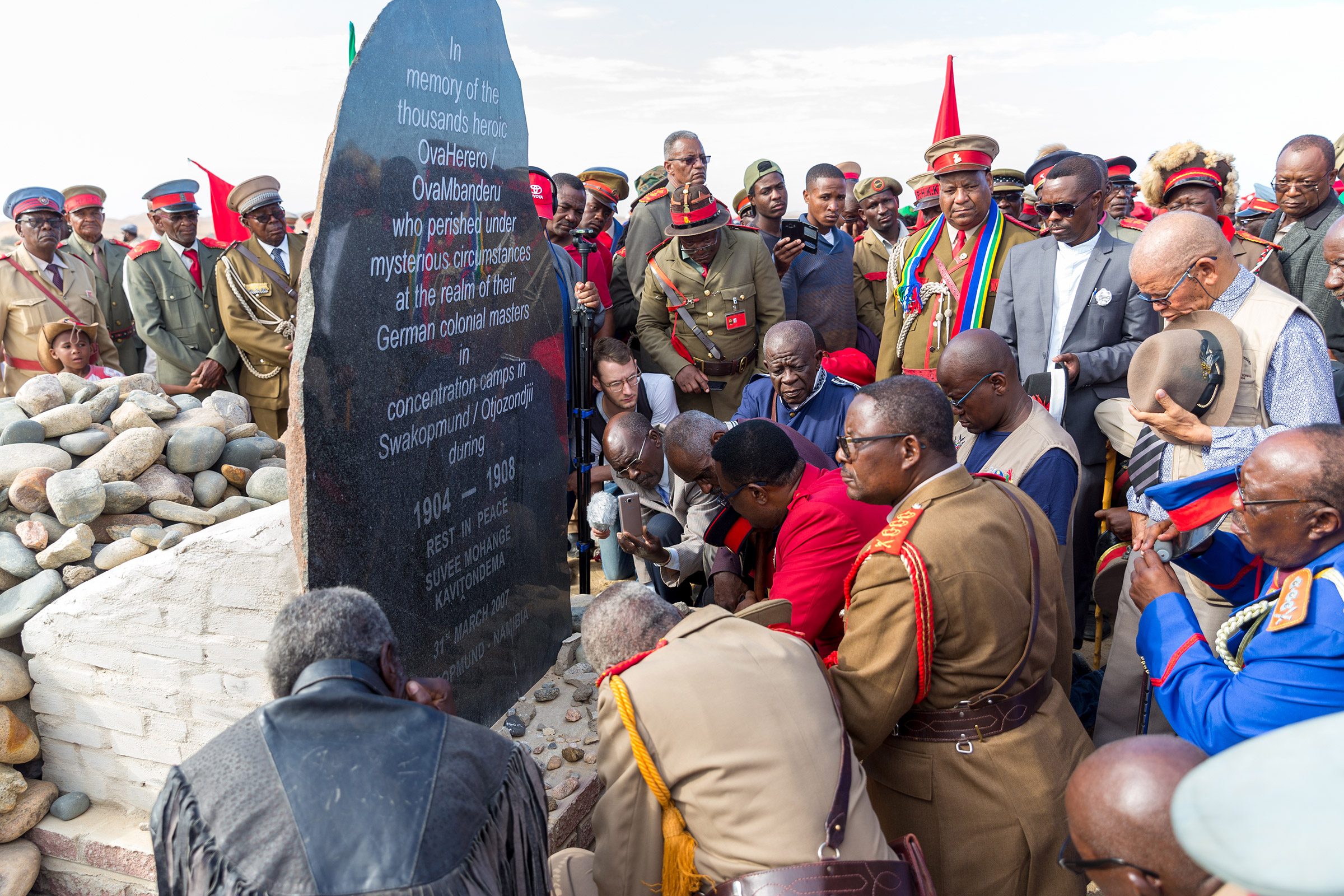 Paramount Chief Adv. Vekuii Rukoro, high-ranked chiefs and other members of the Herero and Nama communities gather around a monument in honor of the Ovaherero and Nama people that were victims of the genocide by German colonial forces at the Swakopmund Concentration Camp Memorial, in Swakopmund, Namibia, as a part of the Reparation Walk 2019 on March 30, 2019.