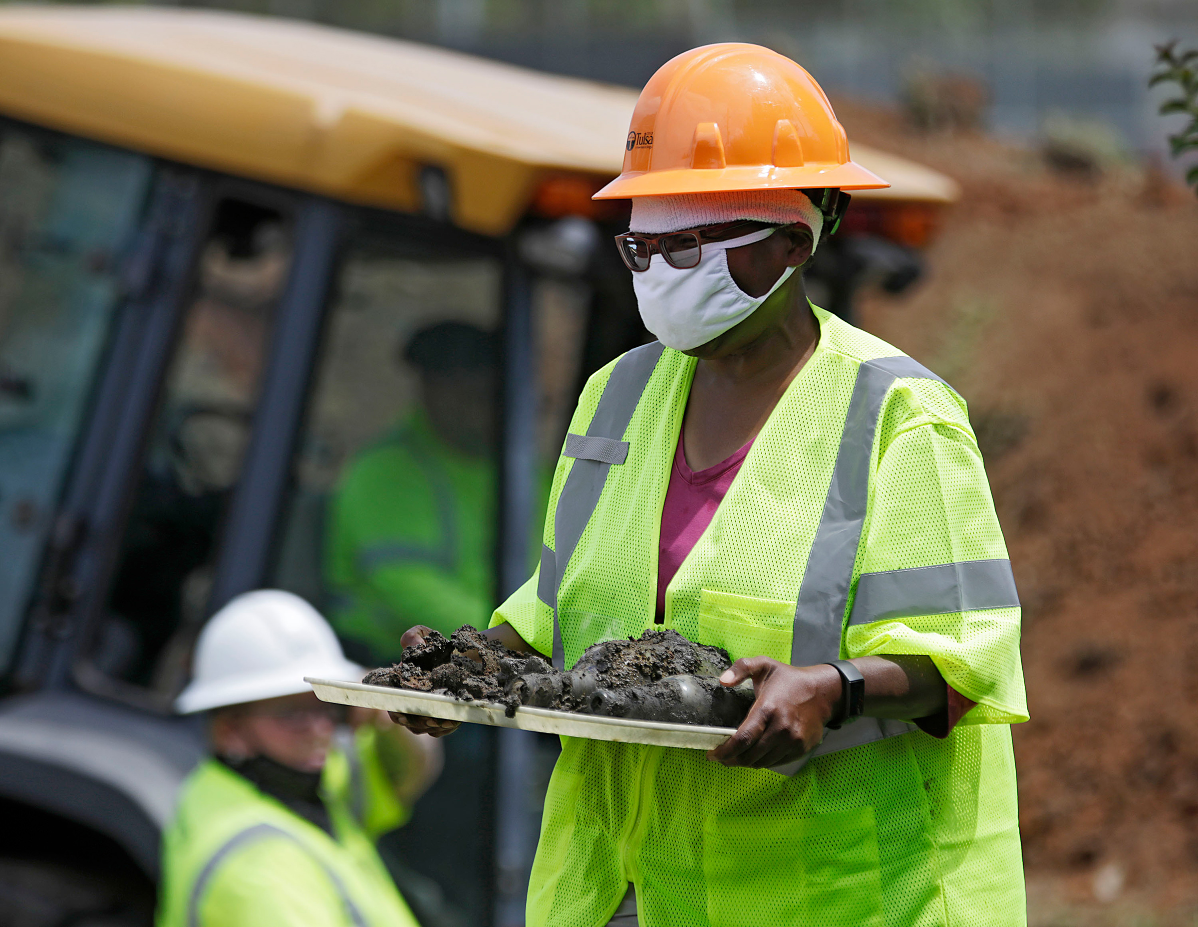 Forensic anthropologist Phoebe Stubblefield carries a tray of items found at Oaklawn Cemetery during a test excavation in the search for possible mass graves from the 1921 Tulsa Race Massacre in Tulsa, Okla., on July 21, 2020.