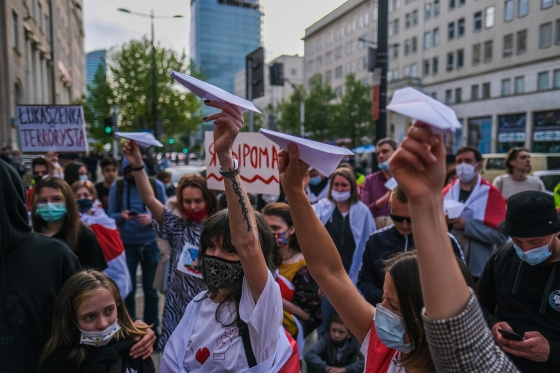 People hold paper airplanes during a protest against the detention of the Belarusian journalist Roman Protasevich in Warsaw on May 24, 2021.
