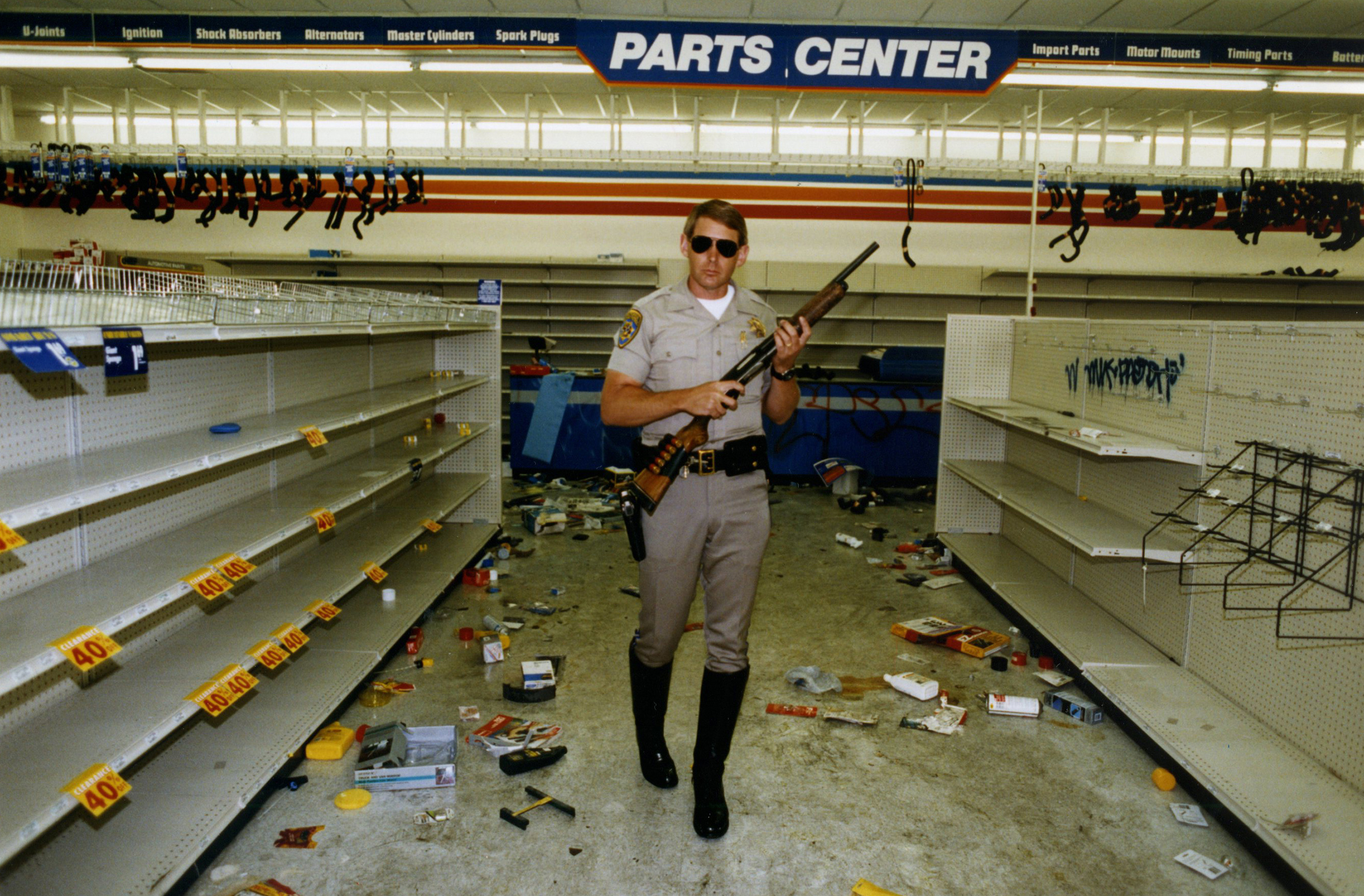 Officer Hugh Gnecco of the California Highway Patrol checks for looters in an auto parts store at Washington Boulevard and Western Avenue during the L.A. riots on May 1, 1992.