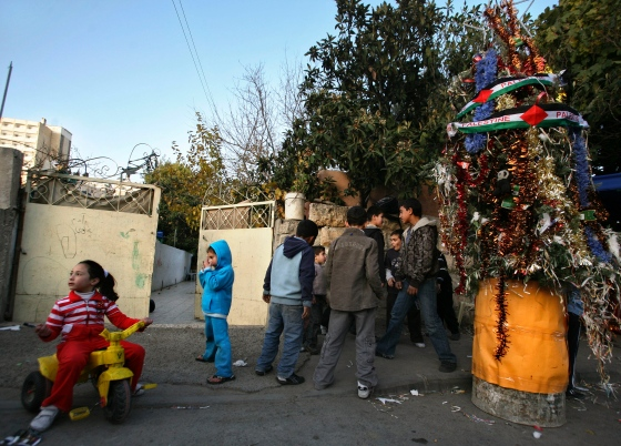 Palestinians gather around a Christmas Tree during a ceremony in the East Jerusalem neighborhood of Sheikh Jarrah on Dec. 23, 2009.