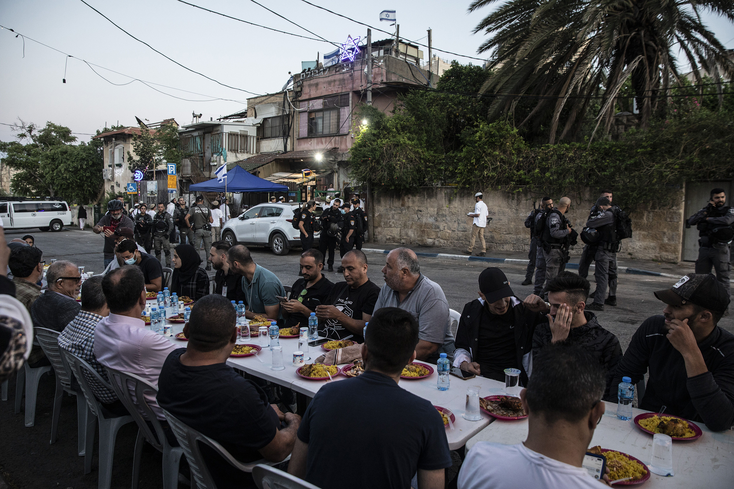 Palestinians sit at a large table to break the fast during Ramadan as Israeli border police guard Jewish settlers, outside one of the homes they have taken over from a Palestinian family and near other homes of Palestinians facing eviction, in the East Jerusalem neighborhood of Sheikh Jarrah on May 7, 2021.