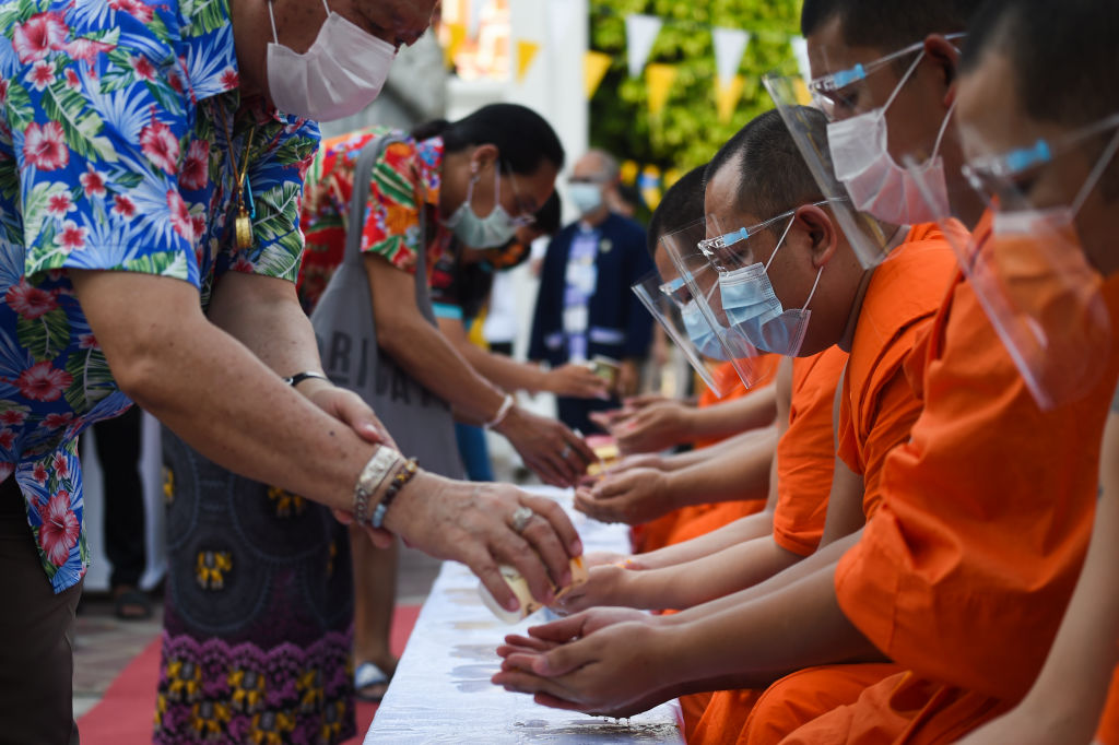People queue to pour water on a Buddhist statue as they celebrate Songkran, also known as the Thai New Year, at Wat Pho temple in Bangkok, Thailand on 13 April 2021.