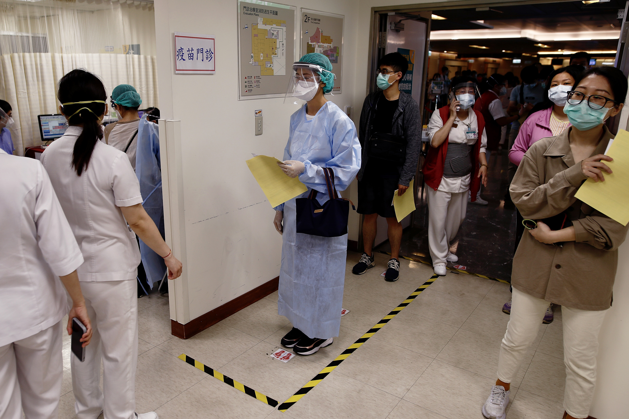 Medical workers wait to receive the AstraZeneca COVID-19 vaccine at a hospital in New Taipei on May 20. Hundreds of frontline workers received the vaccine amid the rising number of cases in Taiwan.
