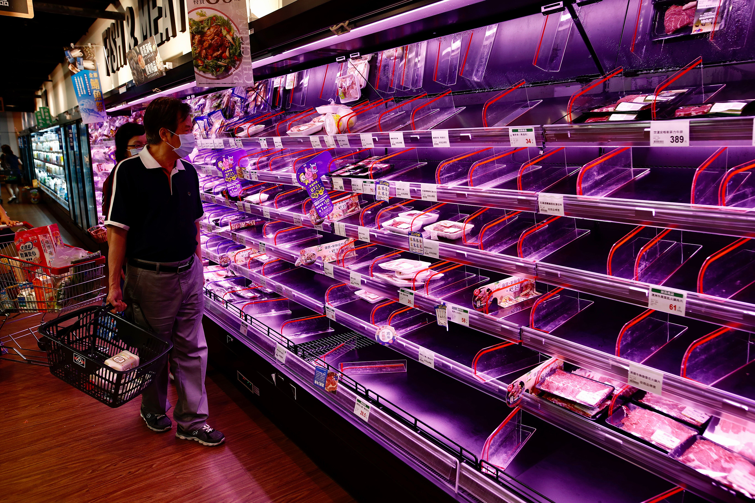 Shoppers check largely empty shelves of meat as they rush to buy grocery essentials inside a supermarket in Taipei on May 17.