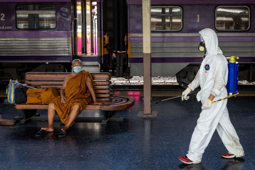 A cleaner wearing personal protective equipment (PPE) walks past a monk wearing a face mask at Hua Lamphong railway station in Bangkok on May 1, 2021, amid the latest wave of COVID-19 coronavirus cases in Thailand.