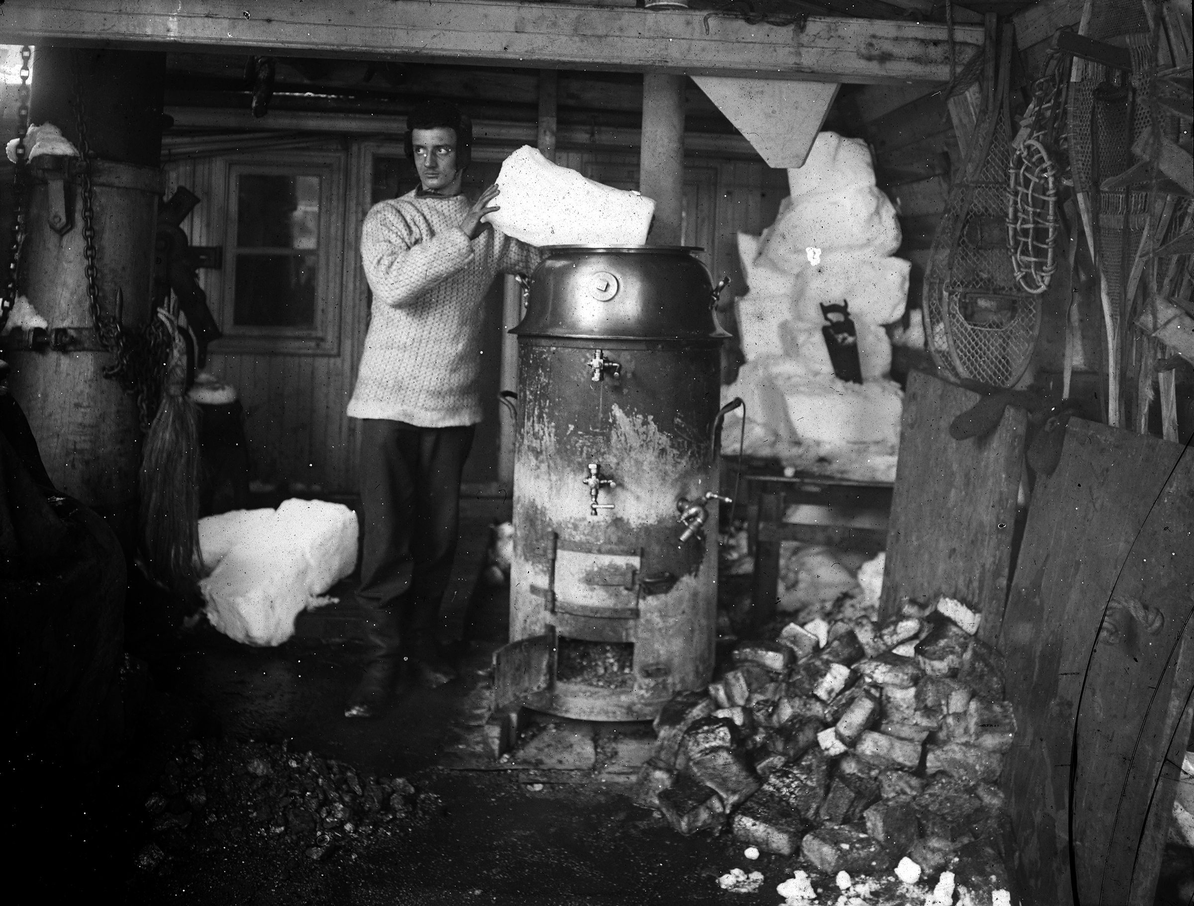 The Belgica's second engineer, Max van Rysselberghe, melts snow on the Belgica's stove.