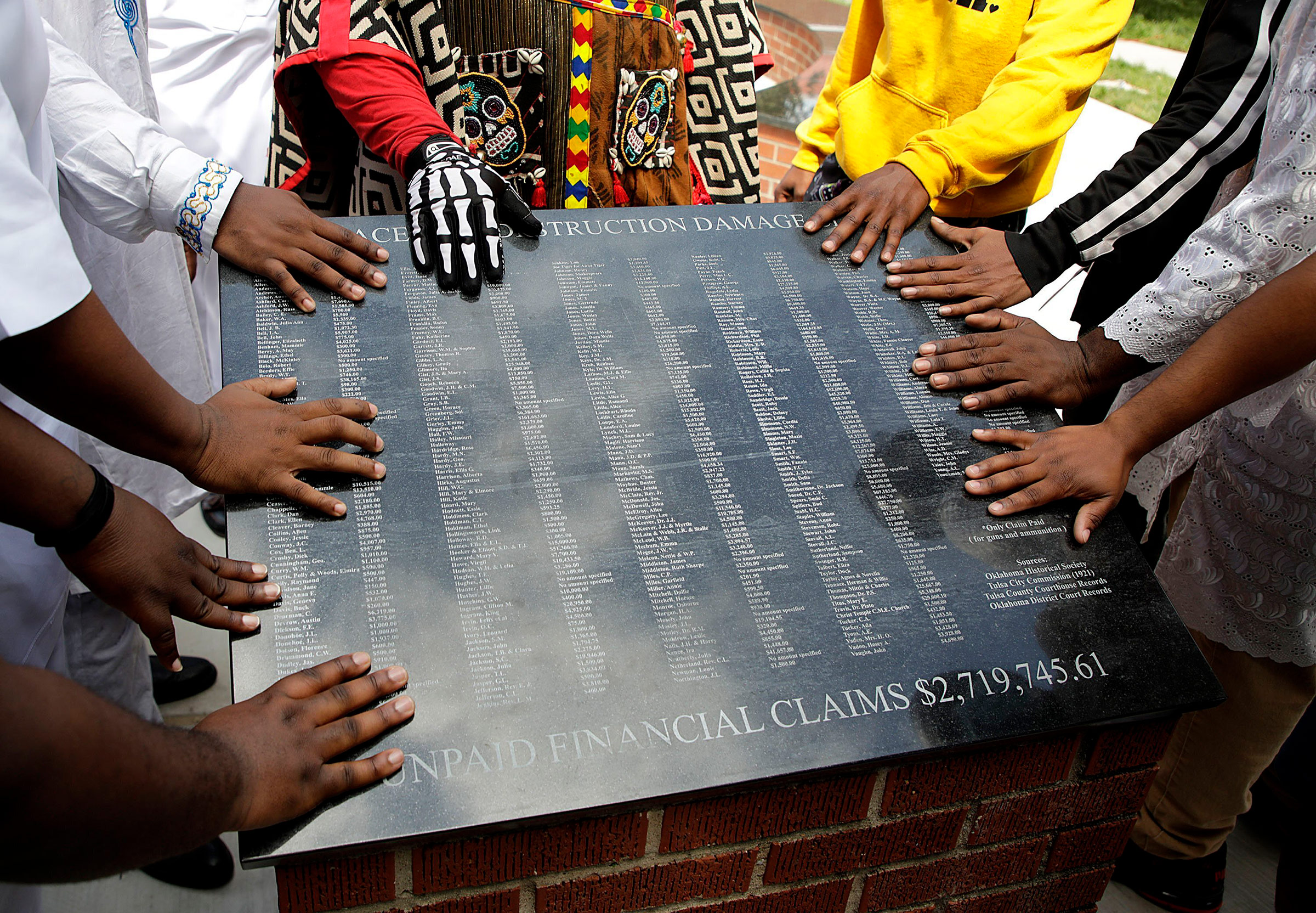 Members of the African Ancestral Society touch the 1921 Black Wall Street Memorial during the Black Wall Street Memorial March in Tulsa on May 28, 2021.