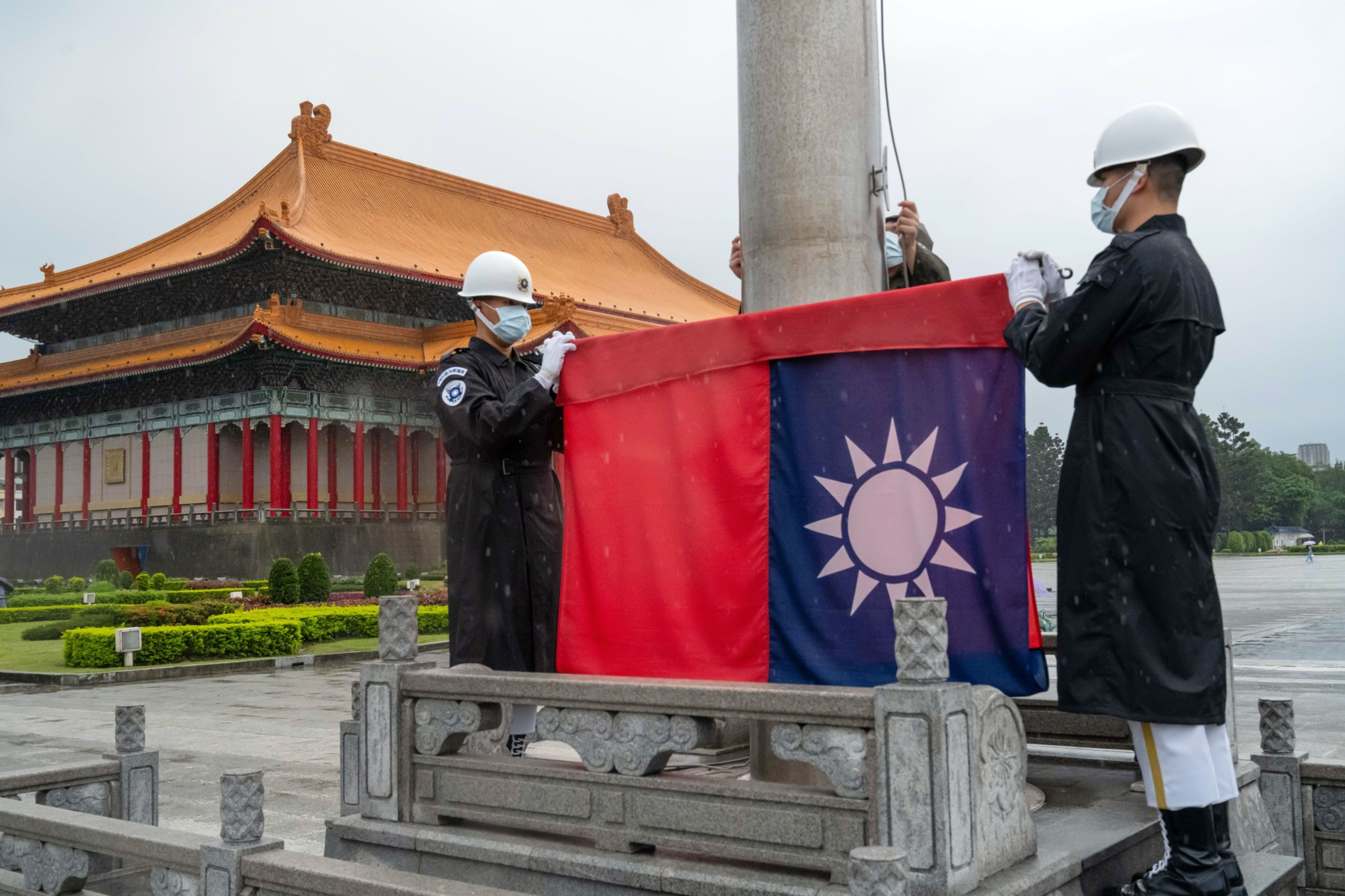 Honor guards wearing protective masks raise a Taiwanese flag at the National Chiang Kai-shek Memorial Hall in Taipei, Taiwan, on Wednesday, June 3, 2021. Taiwan'