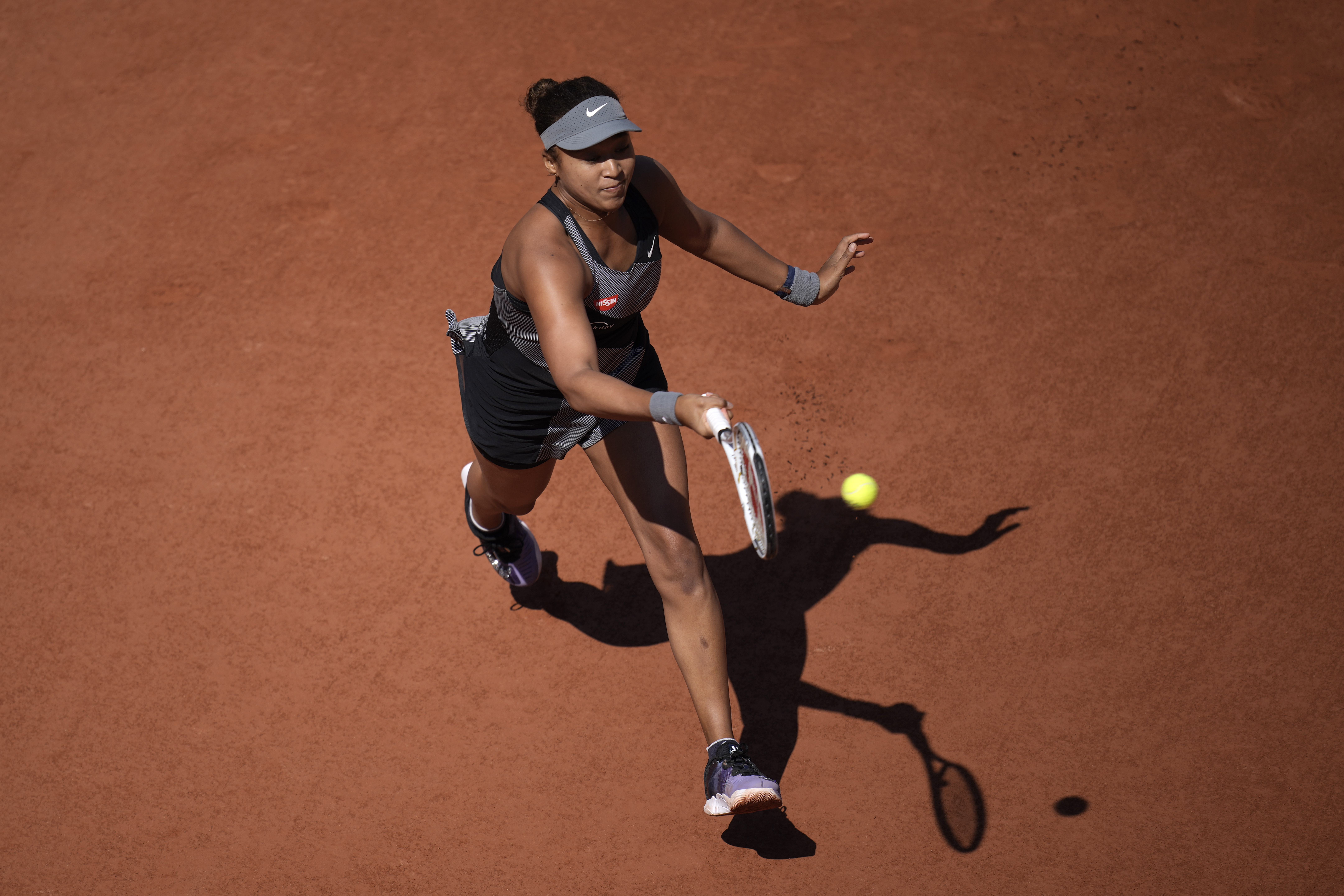 Japan's Naomi Osaka returns the ball to Romania's Patricia Maria Tig during their first round match at the Roland Garros stadium Sunday, May 30, 2021 in Paris.