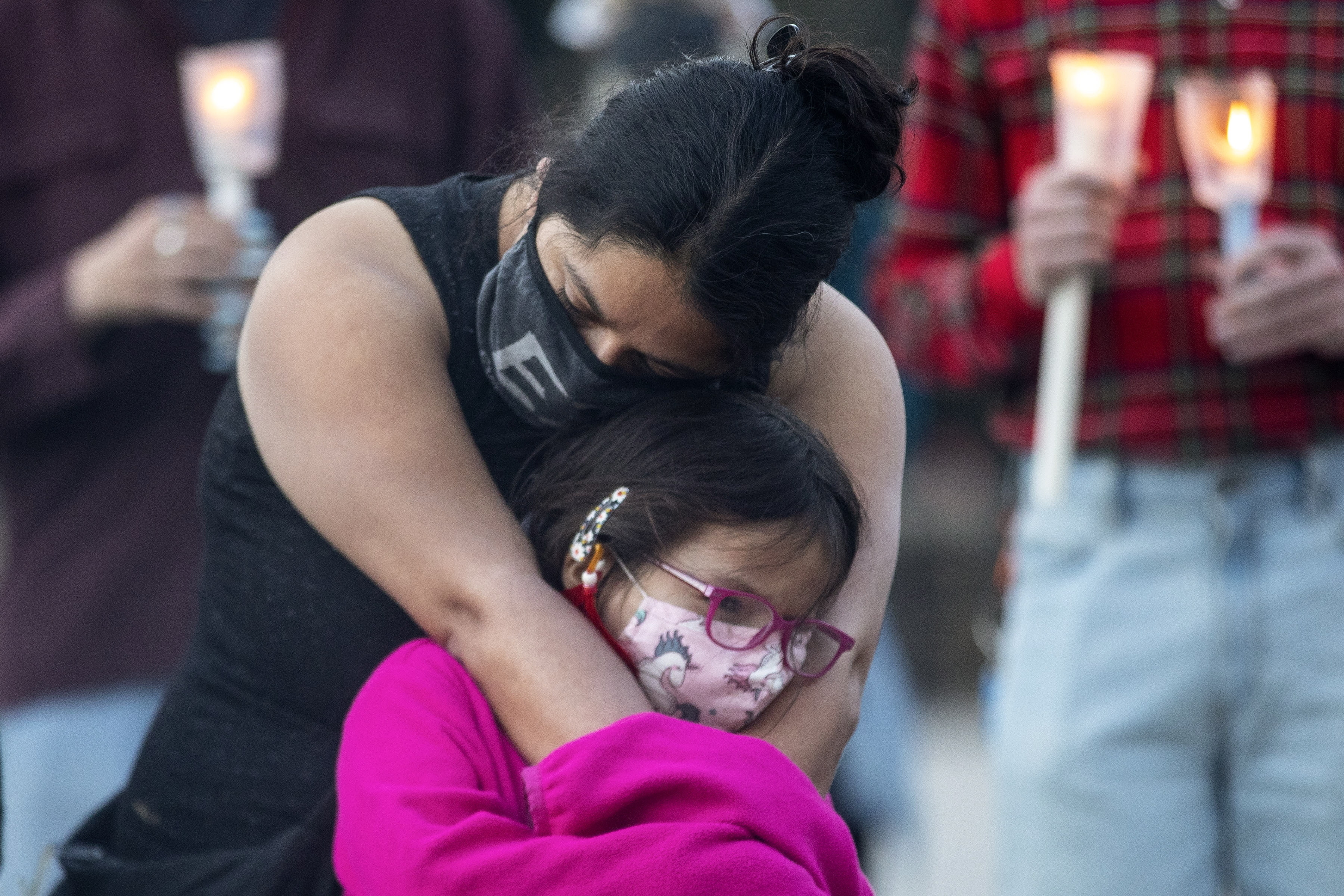 A mother hugs her daughter during a vigil in Toronto on Sunday May 30, 2021, for the 215 Indigenous children, whose remains were uncovered on the grounds of a former residential school near Kamloops, British Columbia.