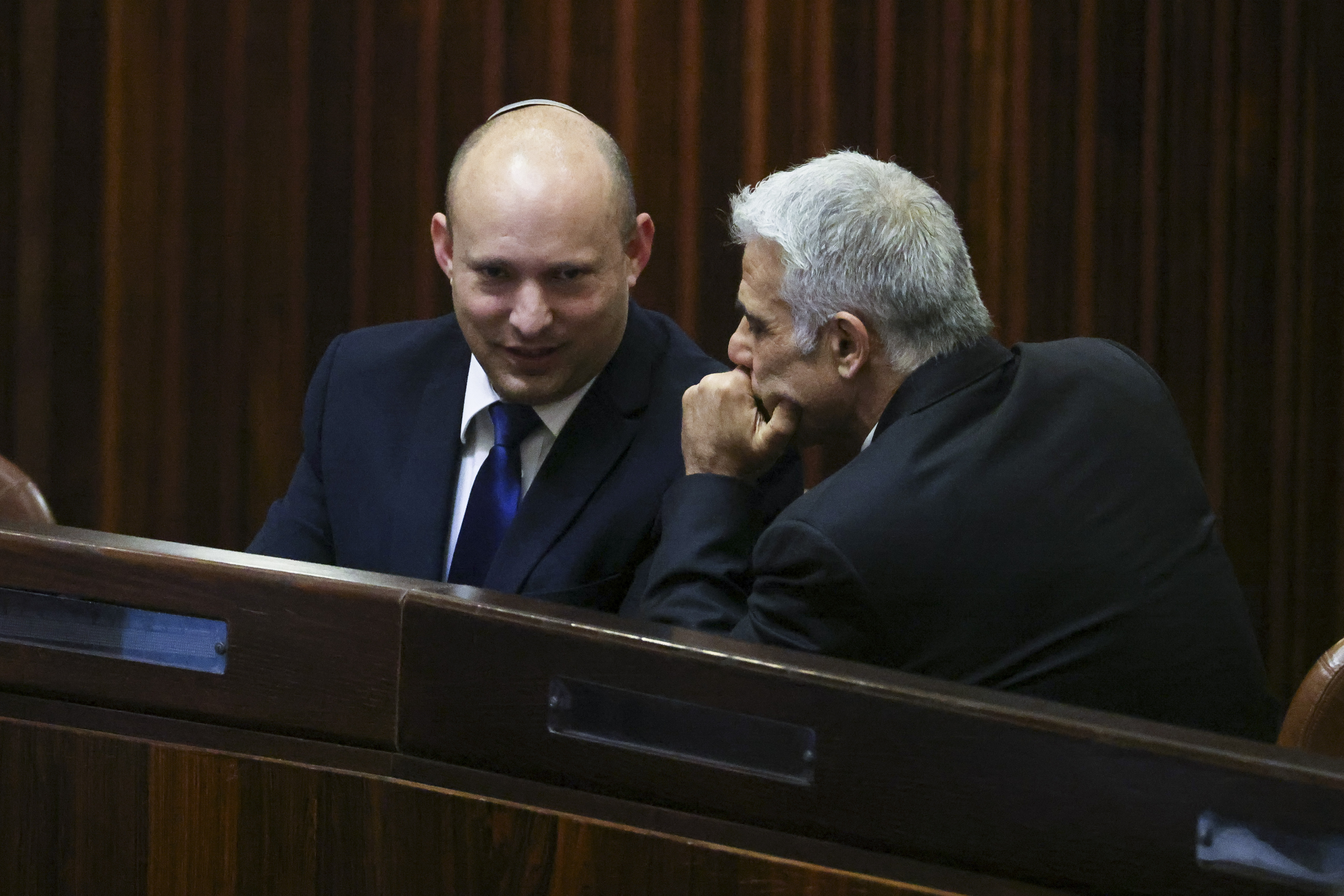 Yamina party leader Naftali Bennett, left, smiles as he speaks to Yesh Atid party leader Yair Lapid during a special session of the Knesset in Jerusalem on Wednesday, June 2, 2021.