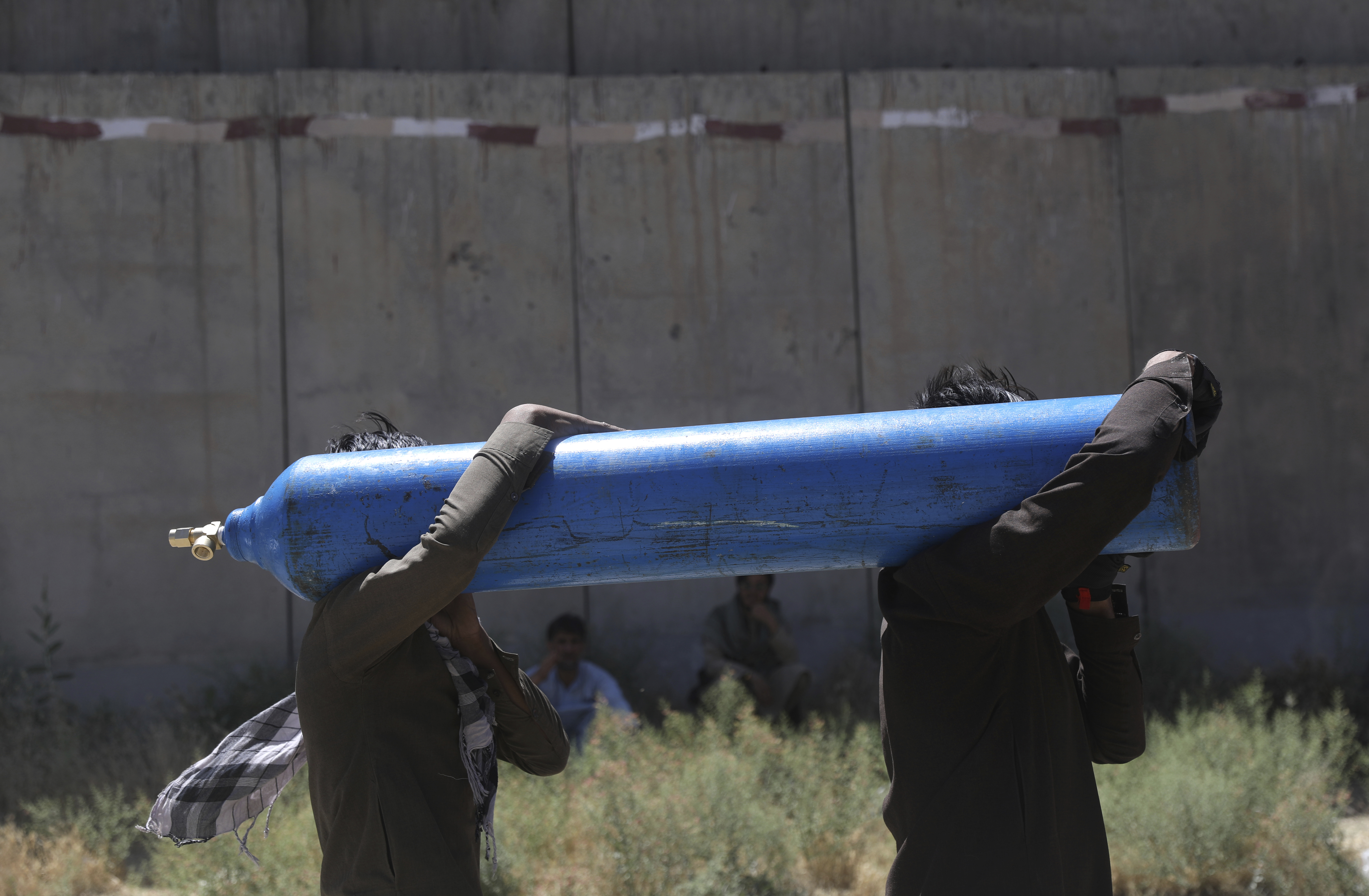 Men carry a cylinder to be refilled from a privately owned oxygen factory, in Kabul, Afghanistan, on June 19, 2021.