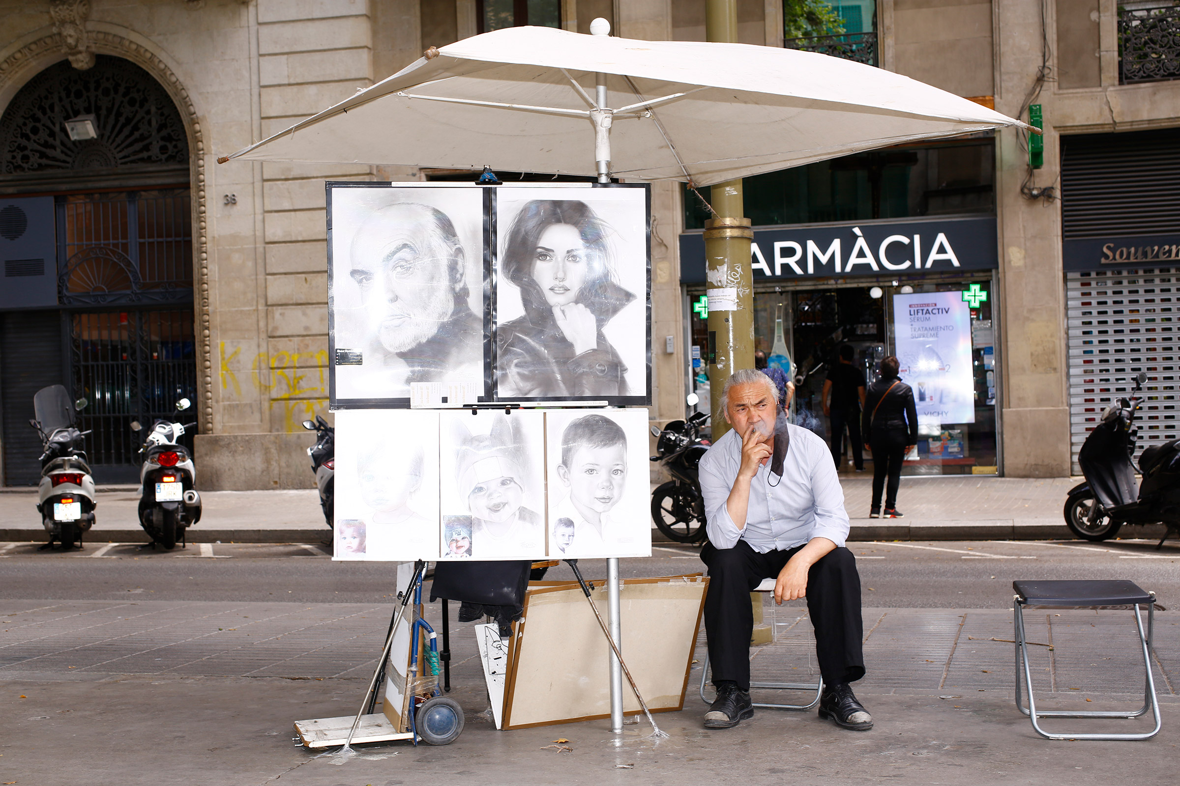 An artist in Las Ramblas takes a smoke break while waiting for customers on June 6