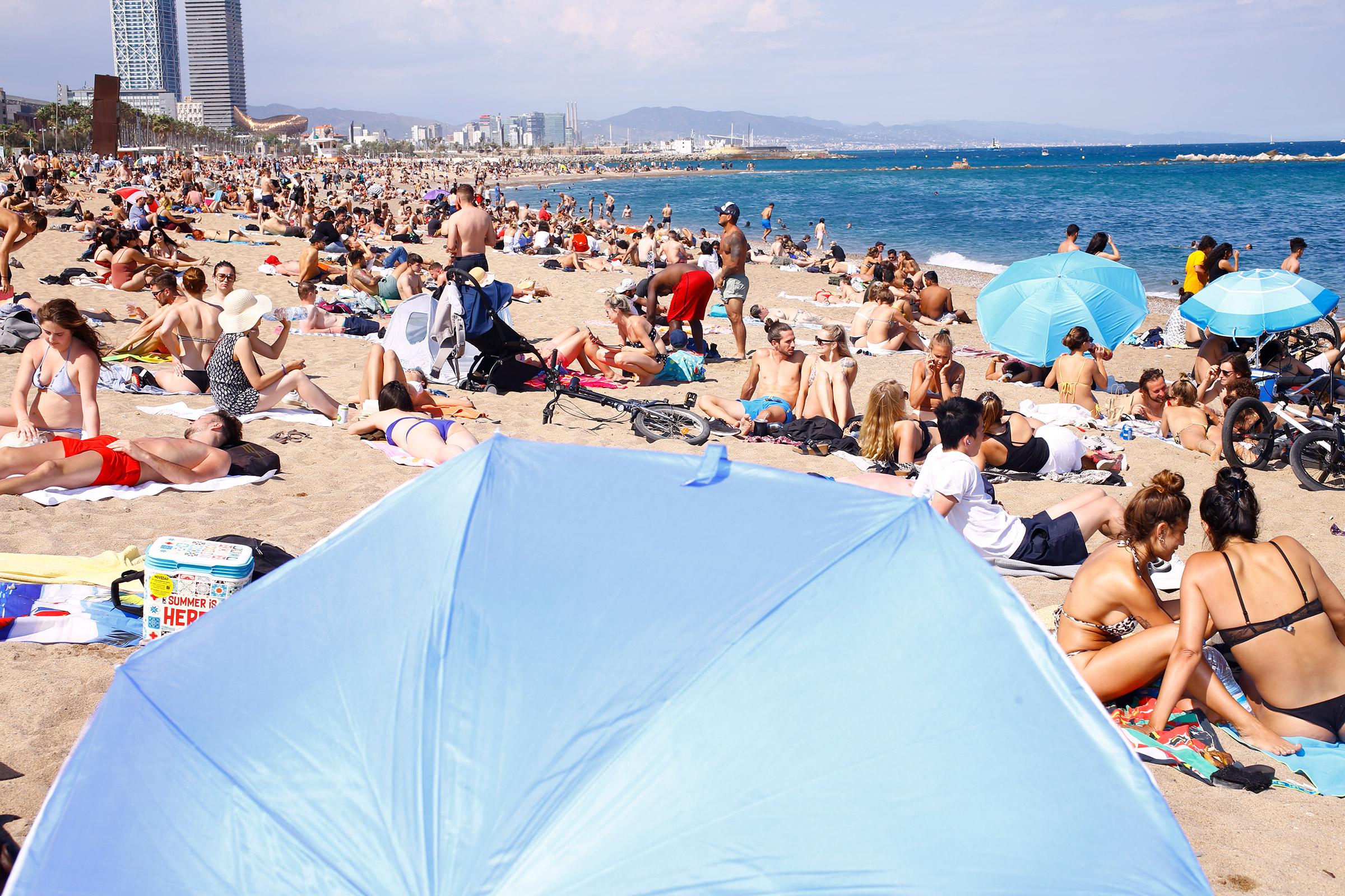 Sunbathers enjoy the busy Barceloneta Beach on June6, 2021.