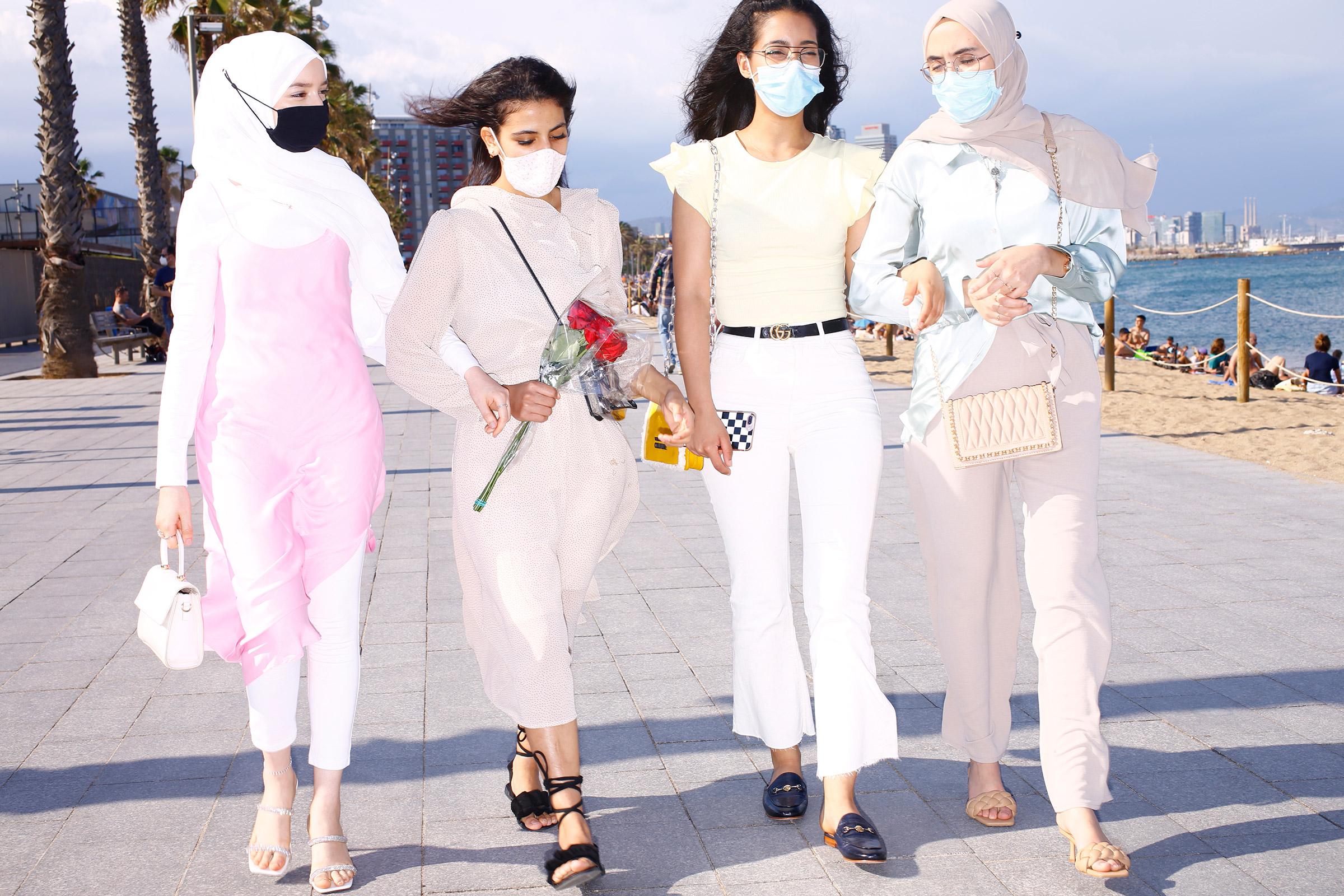 Young women stroll along Barceloneta Beach on June 6.