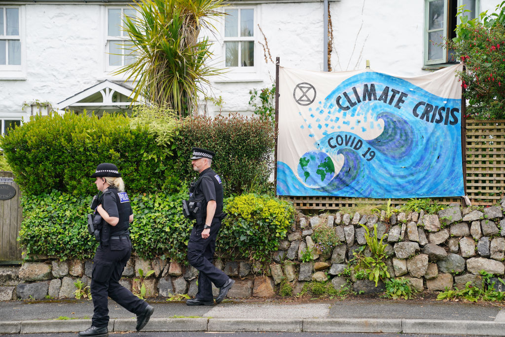 Police officers walk past a banner regarding climate change in Carbis Bay, ahead of the G7 summit in Cornwall. Picture date: Thursday June 10, 2021.