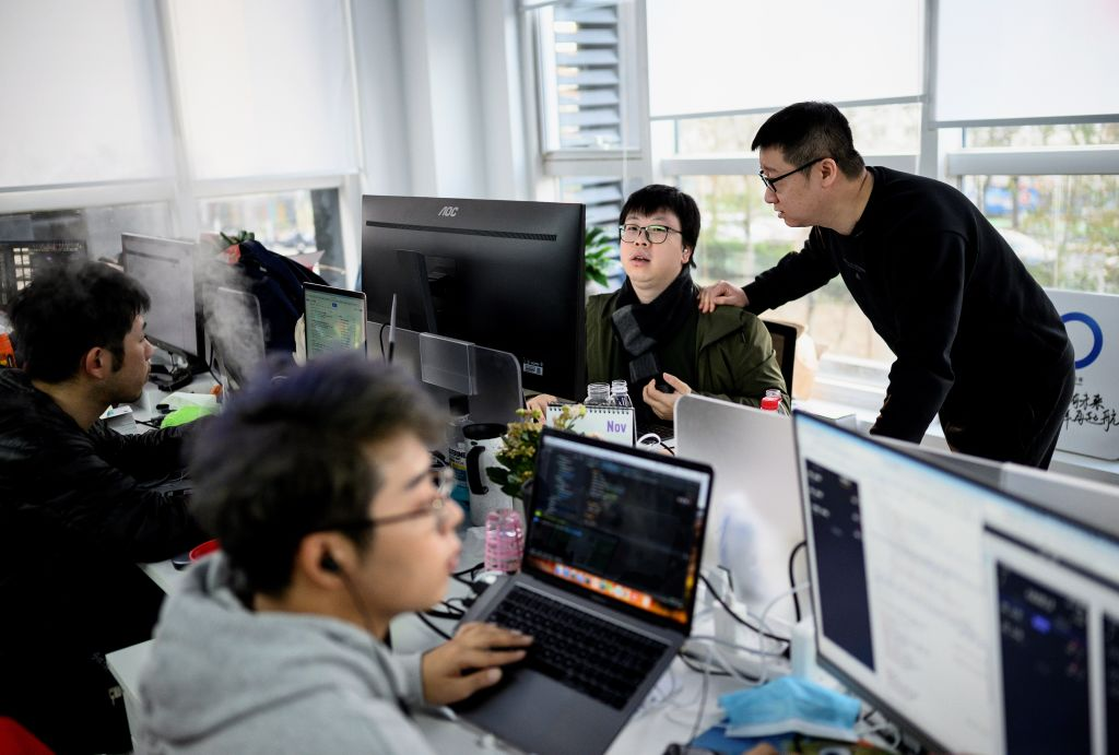 This picture taken on December 10, 2020 shows BlueCity CEO, Ma Baoli (R), talking to an employee at the BlueCity headquarters in Beijing. -