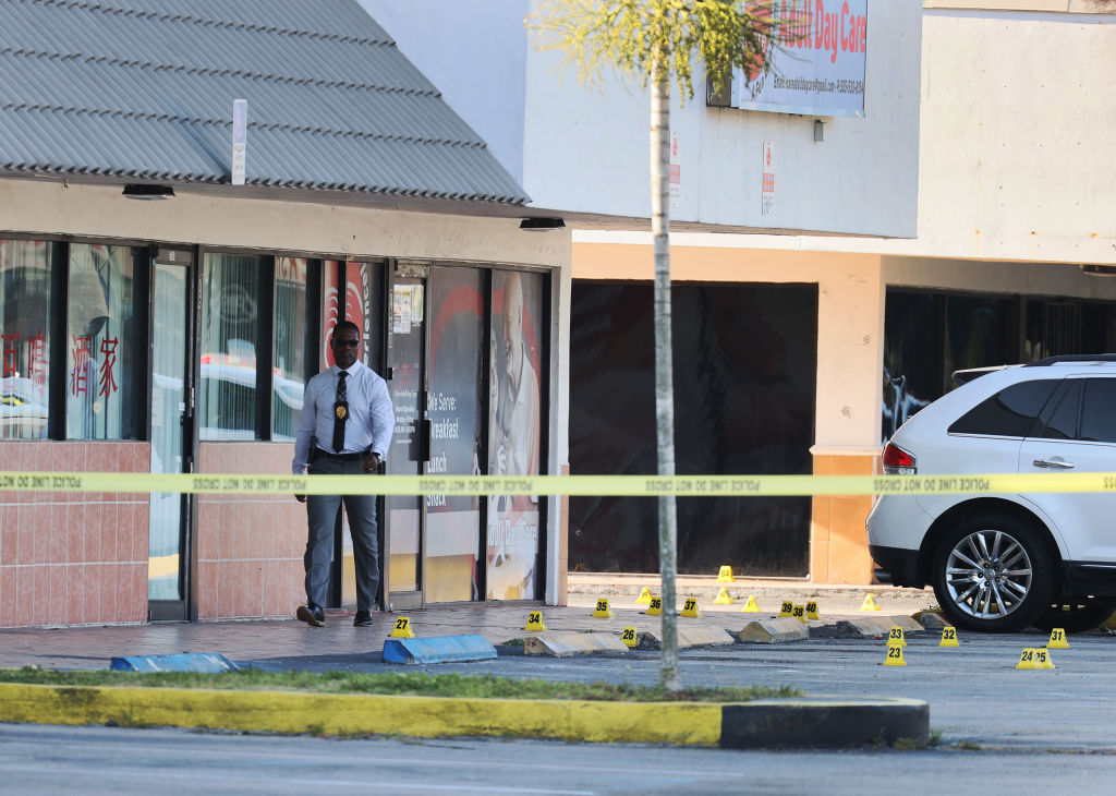 A Miami-Dade police officer investigates near shell case evidence markers on the ground where a mass shooting took place outside of a banquet hall on May 30, 2021 in Hialeah, Florida. Halfway through the year, gun violence continues to plague American communities at obscenely high levels.