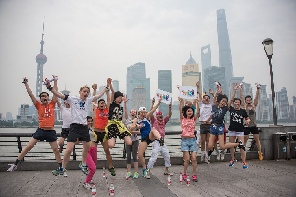 Participants of the ShanghaiPRIDE run pose for pictures during a break on the Bund in front of the financial district of Pudong in Shanghai on June 13, 2015.