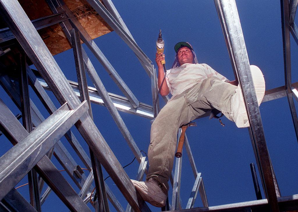 Charlie Martinez installs steel framework in a house under construction in Mission Viejo, Calif.