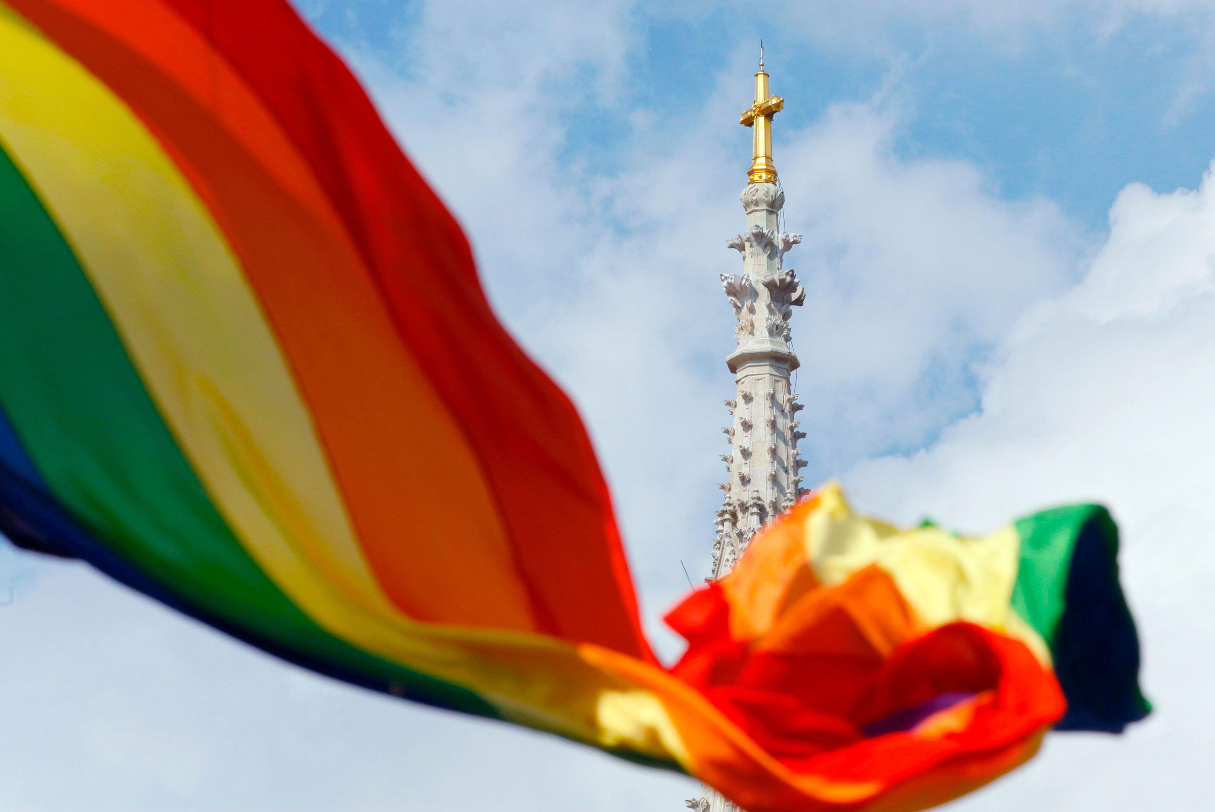 A rainbow flag is seen in front of a church.