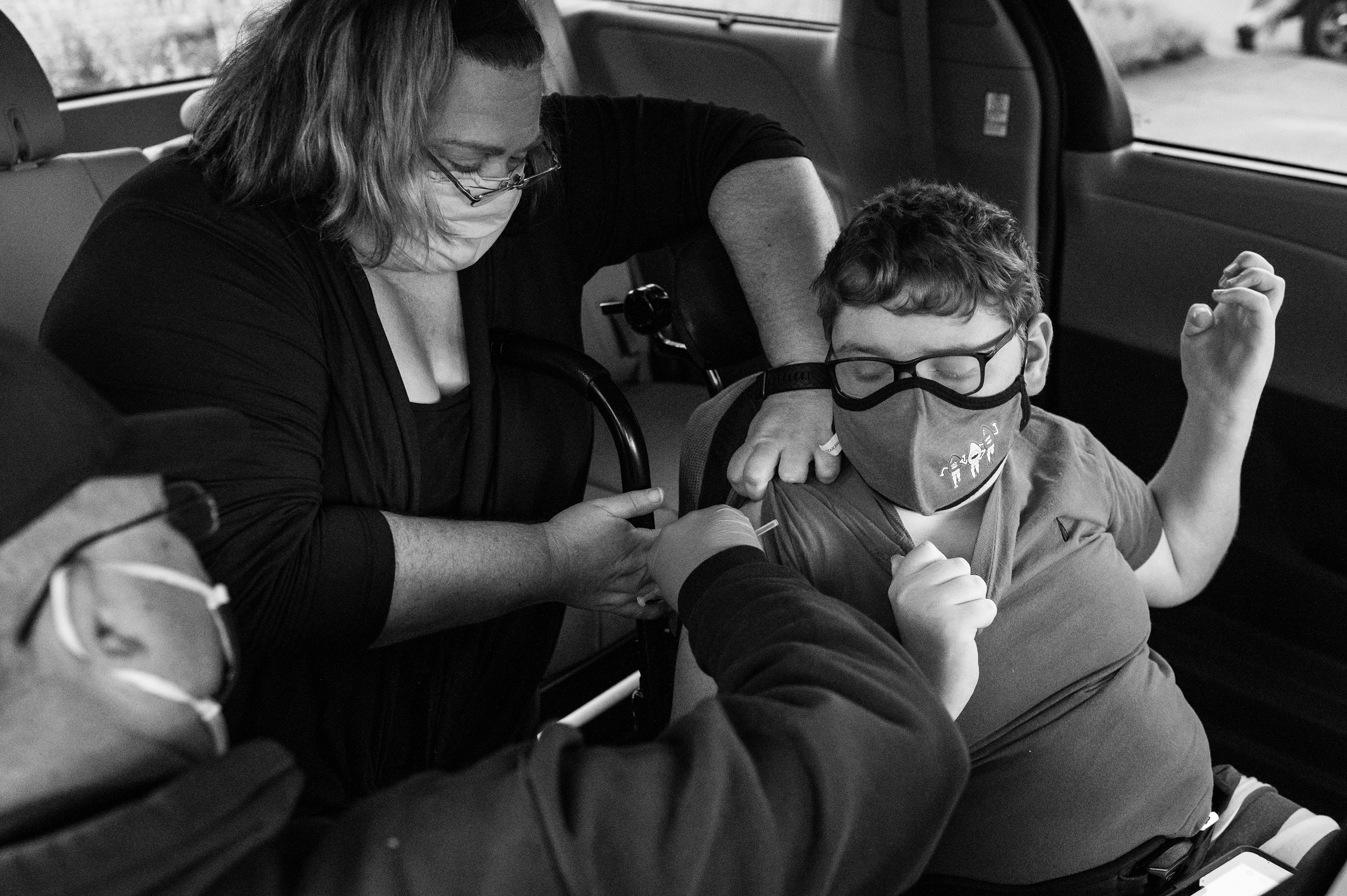 Allison Bungard helps her son Andrew, 13, who has cerebral palsy and Factor V Leiden thrombophilia, receive his shot at a vaccine clinic in Charleston.