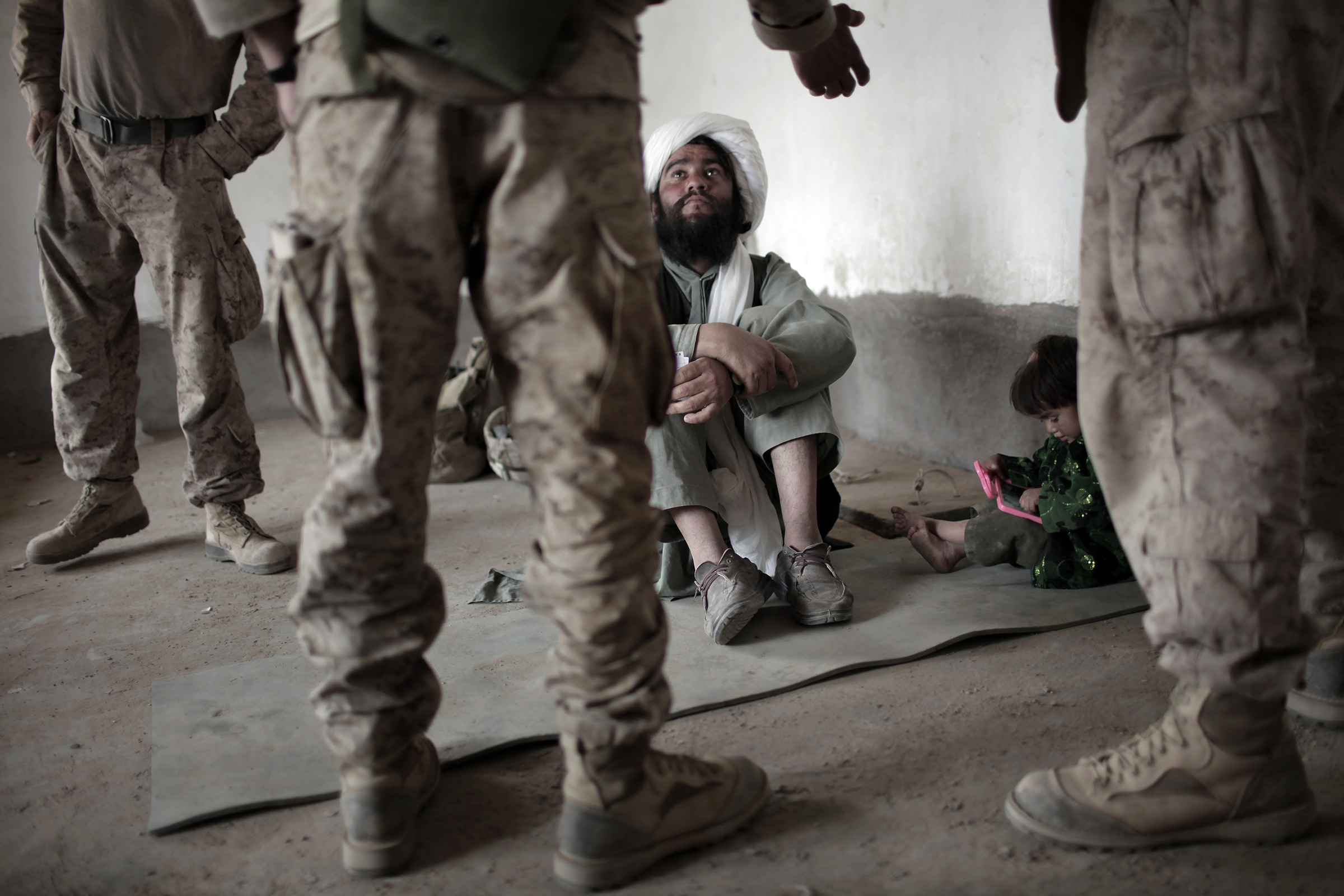 An imam listens to an interpreter for U.S. forces in Marjah, southern Afghanistan, in 2010.