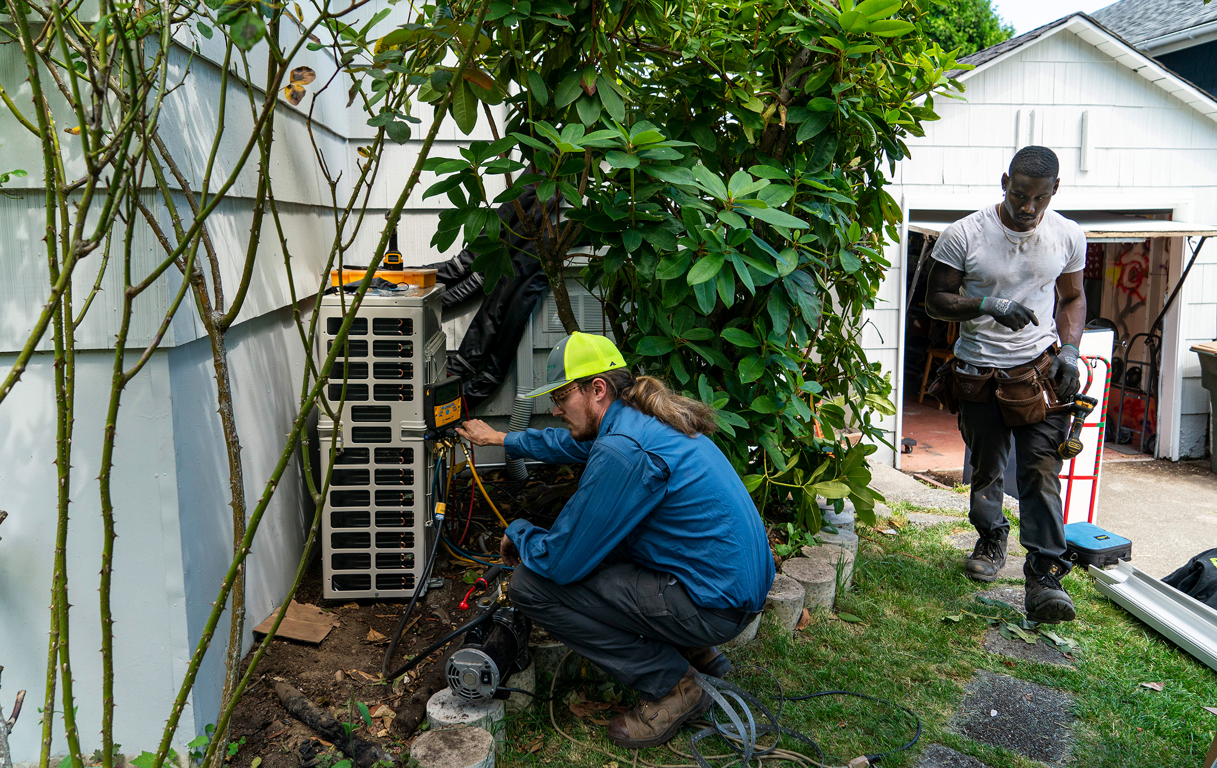 Luke Peters, left, and Elliott Thomas install a mini-split heating and air conditioning system at a home in Seattle on June 23, 2021. A heat wave soon set records across the region.