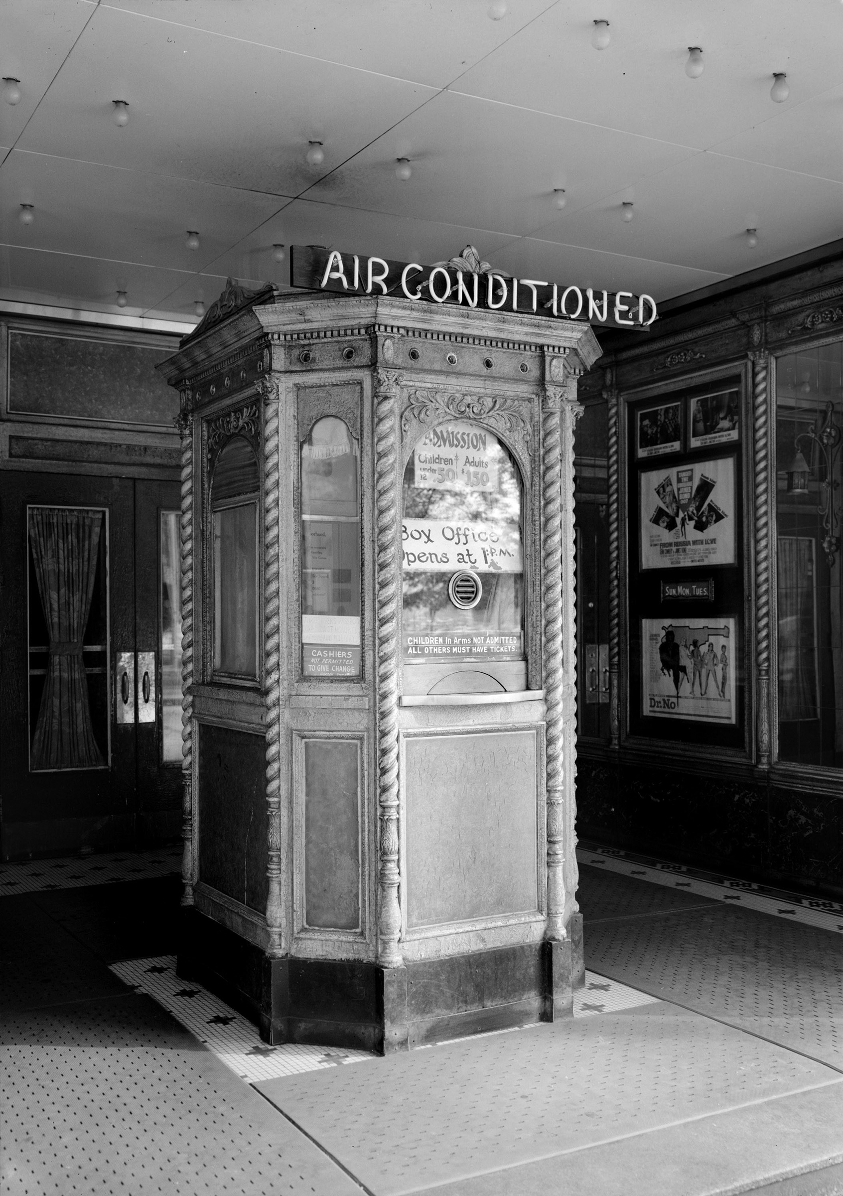 A theater's lobby advertises air conditioning to prospective movie-goers.